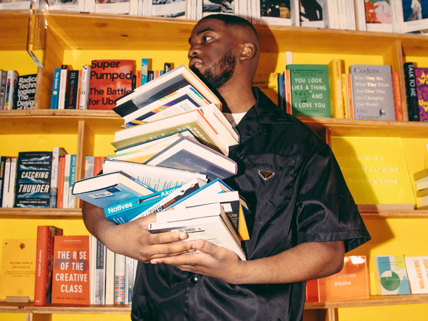 A man holding a pile of books next to a yellow bookshelf.