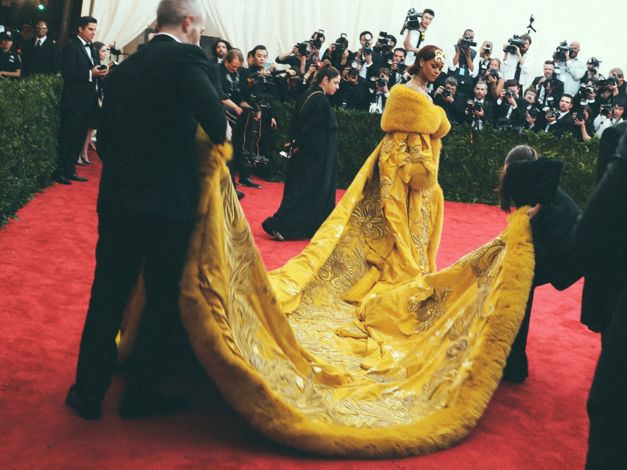 A woman wearing a long flowing yellow dress at a red carpet event.