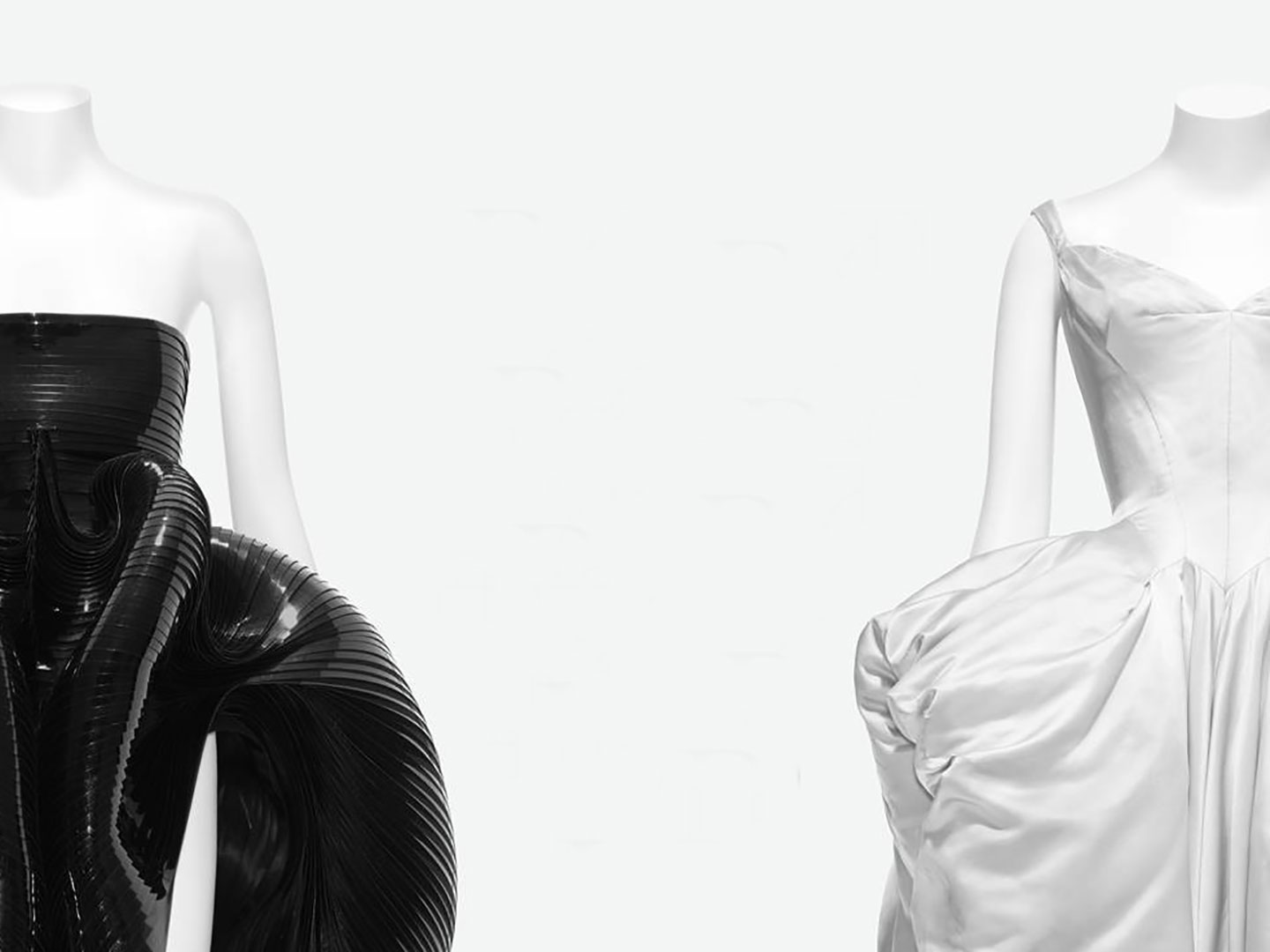 A black outfit and a white outfit on mannequins on a grey background.