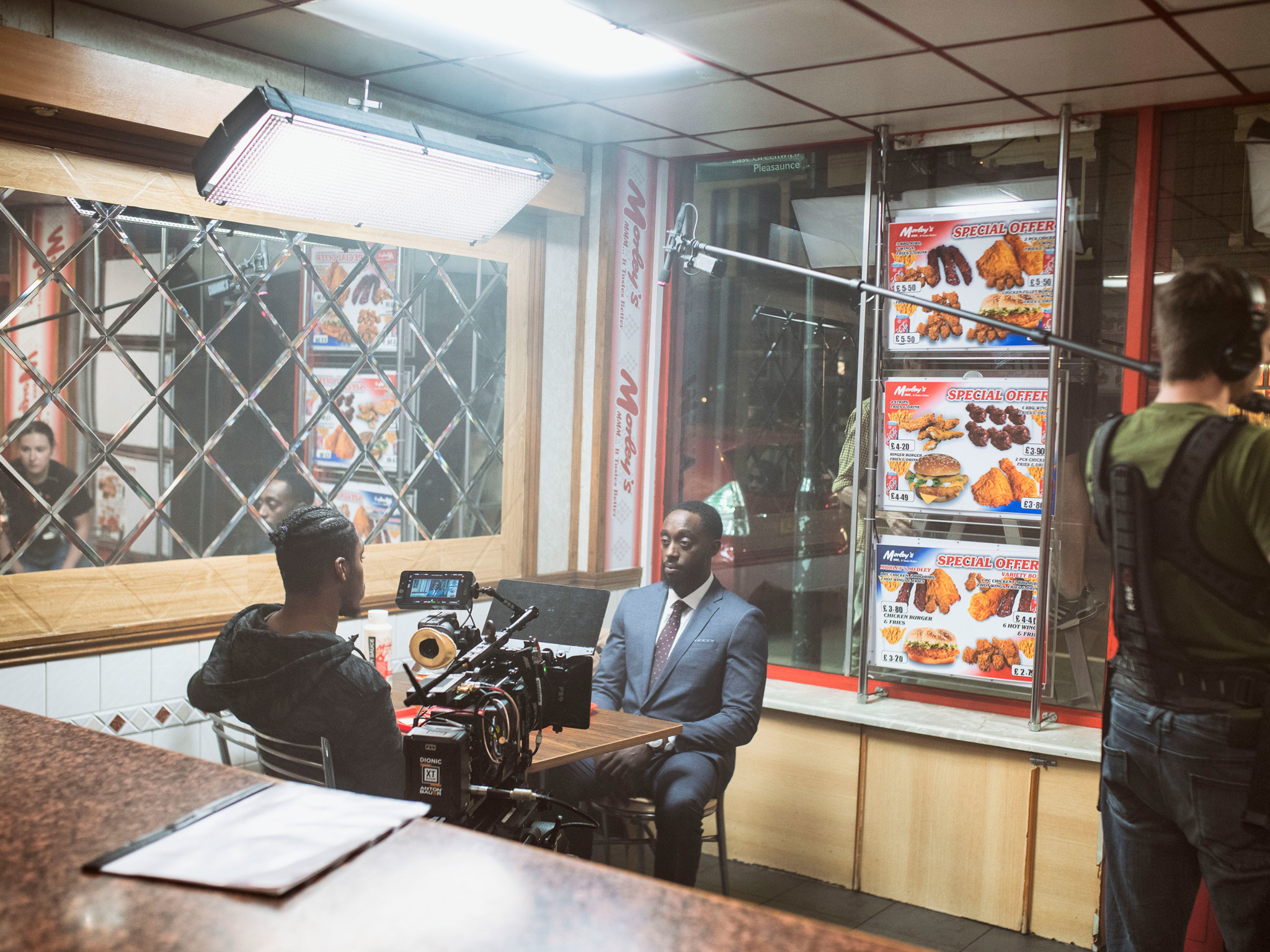 Two men sitting at a table in a chicken shop film set.