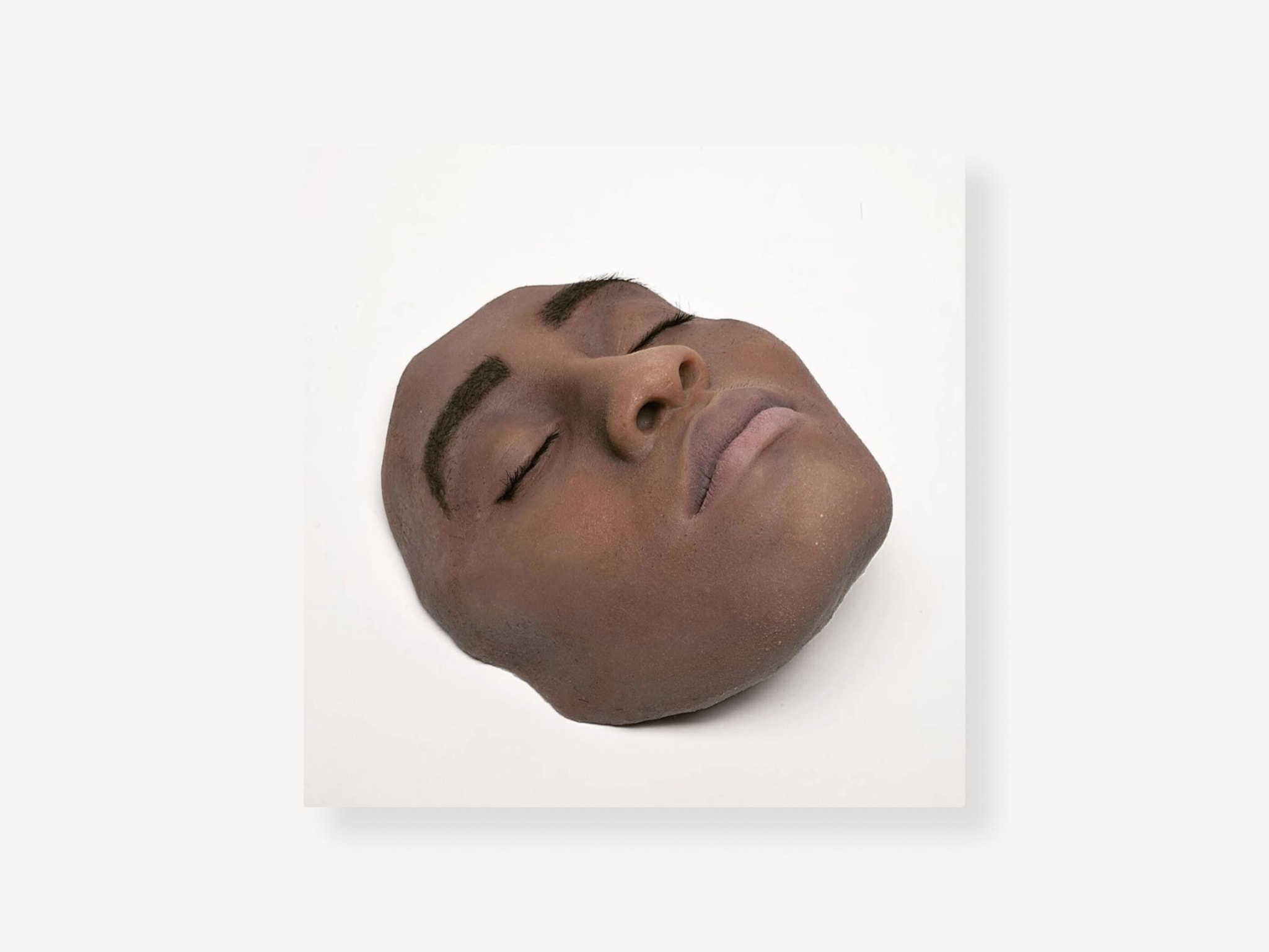 A lifelike sculpture of the front of a person's face on a white block.