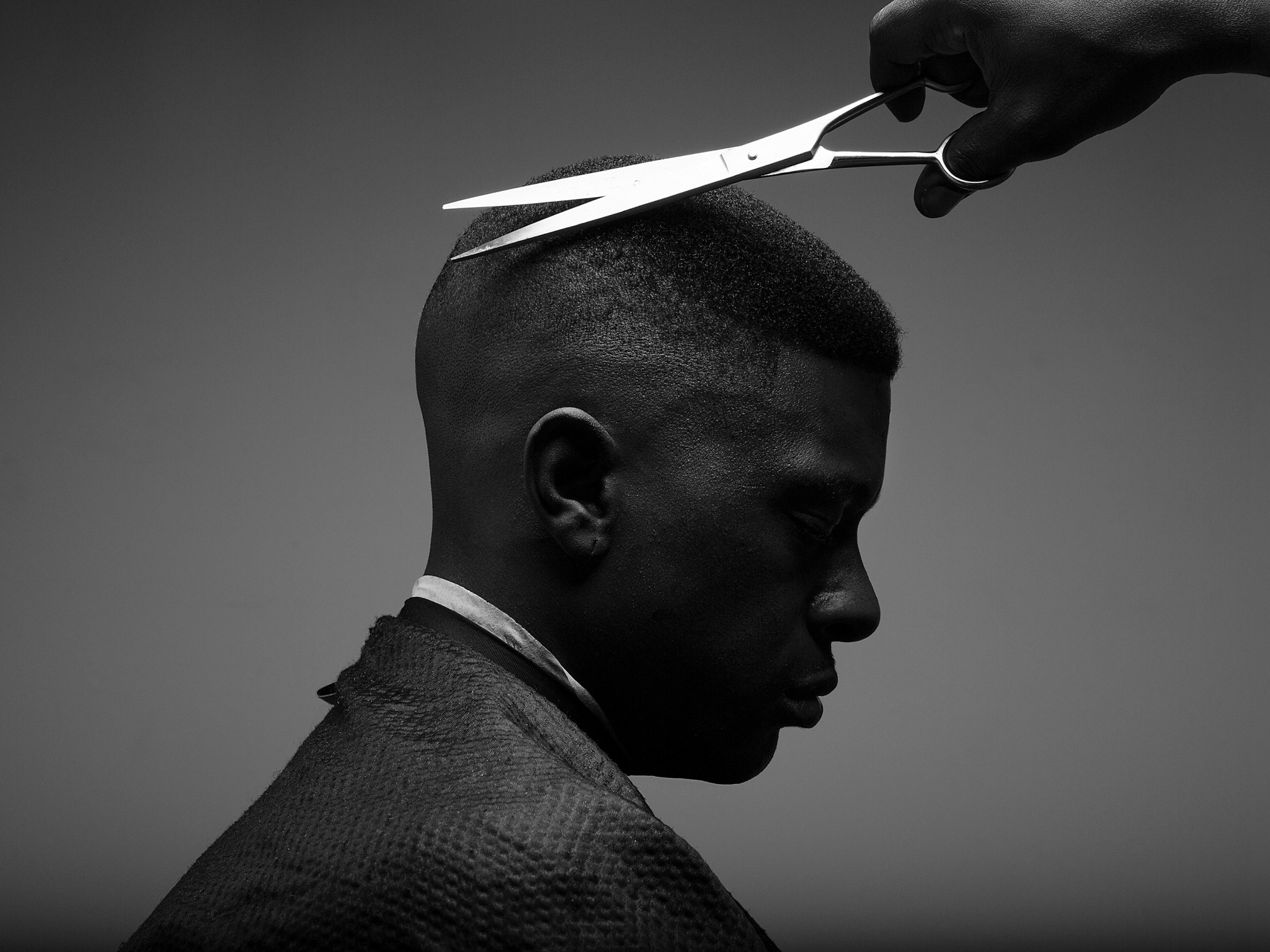 Scissors cutting a man's hair.