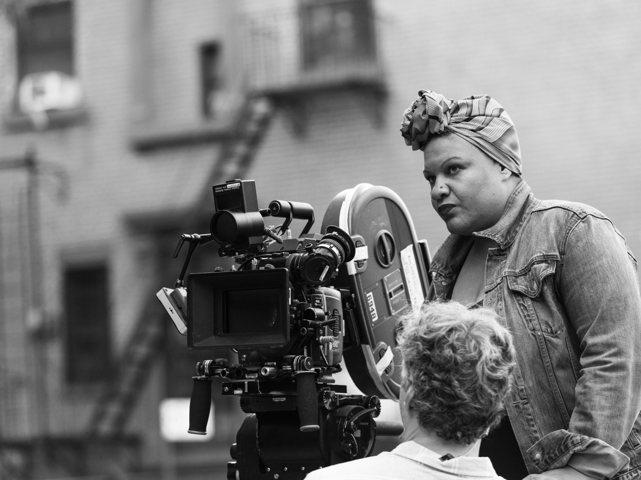 A woman directing next to a large film camera.