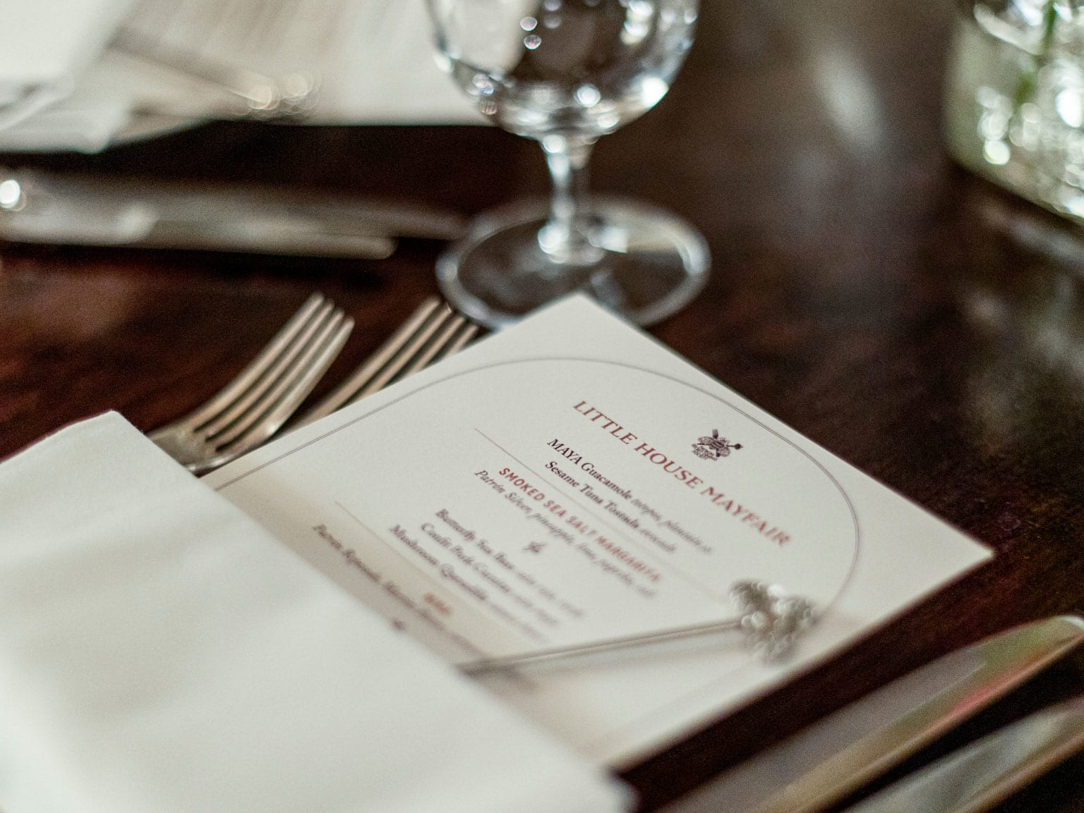 A close up of a laid dining table with tailored menus tucked into serviettes.