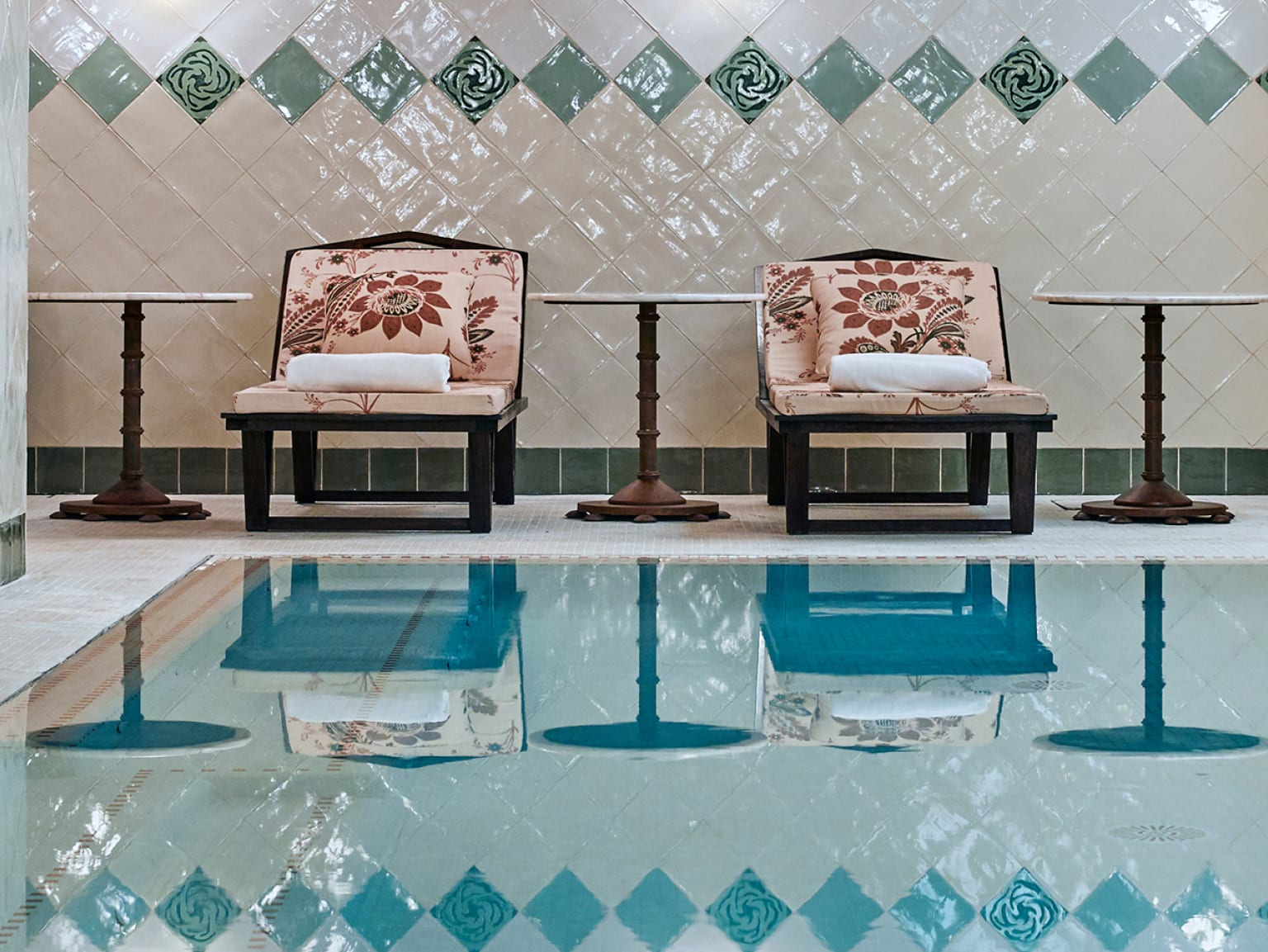Two loungers next to an indoor pool.
