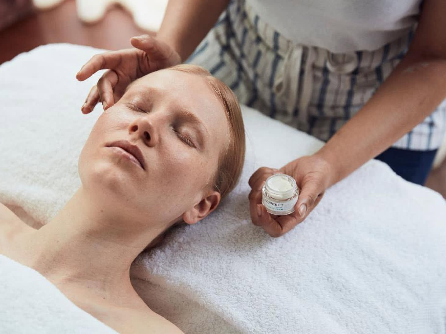 A woman on a bed receiving a facial treatment.