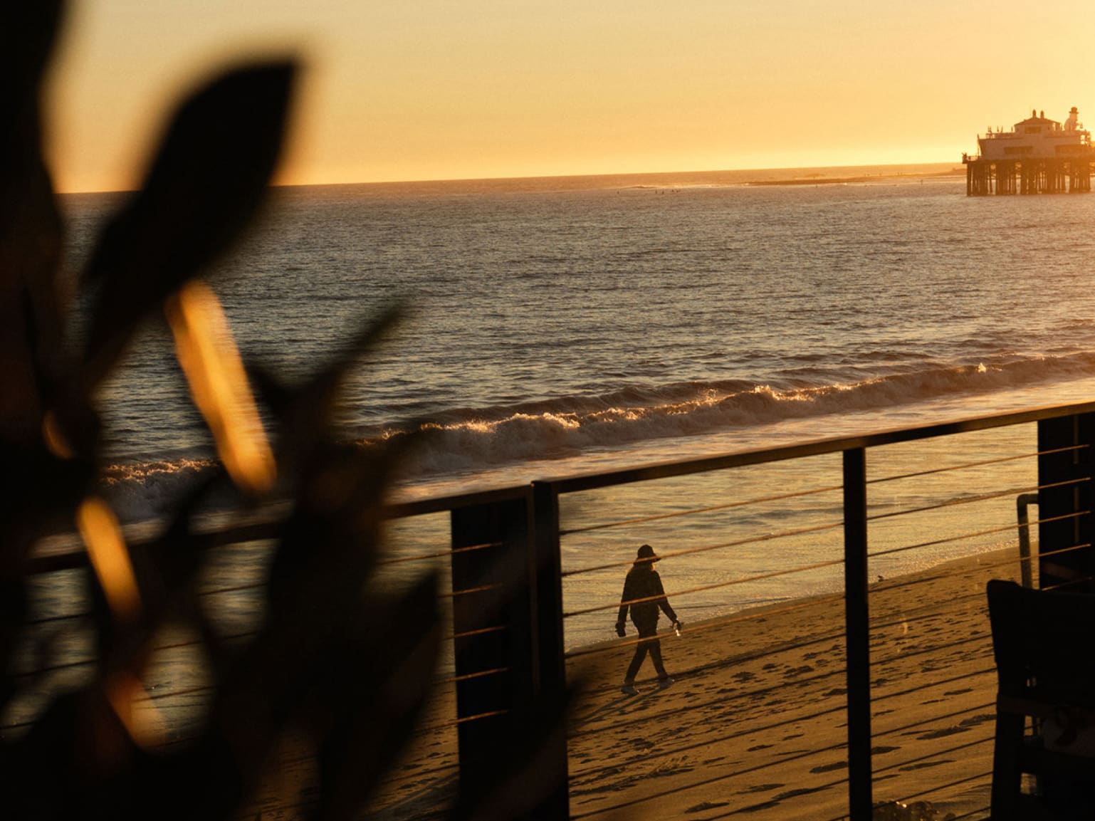 Looking down from a terrace at a person walking on a beach at sunset.
