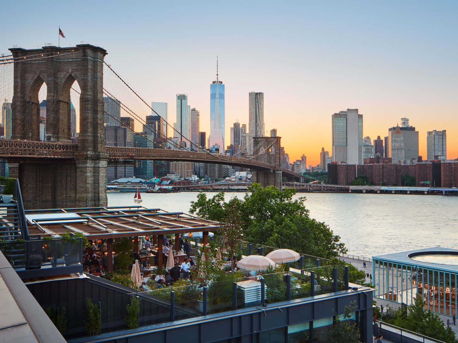 A terrace overlooking the East River, Brooklyn Bridge and the towers of Manhattan.