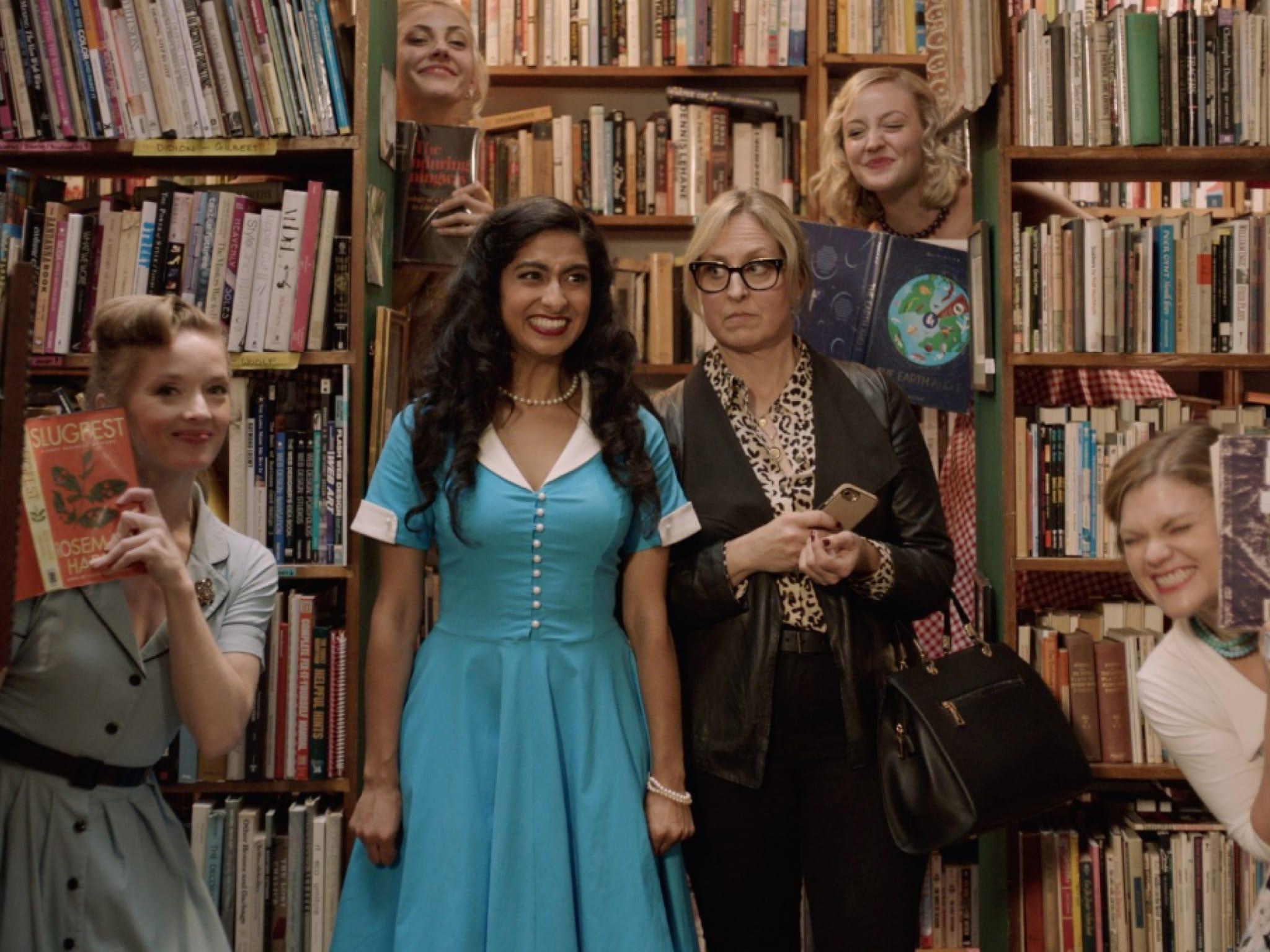 A group of women standing in front of bookshelves full of books.