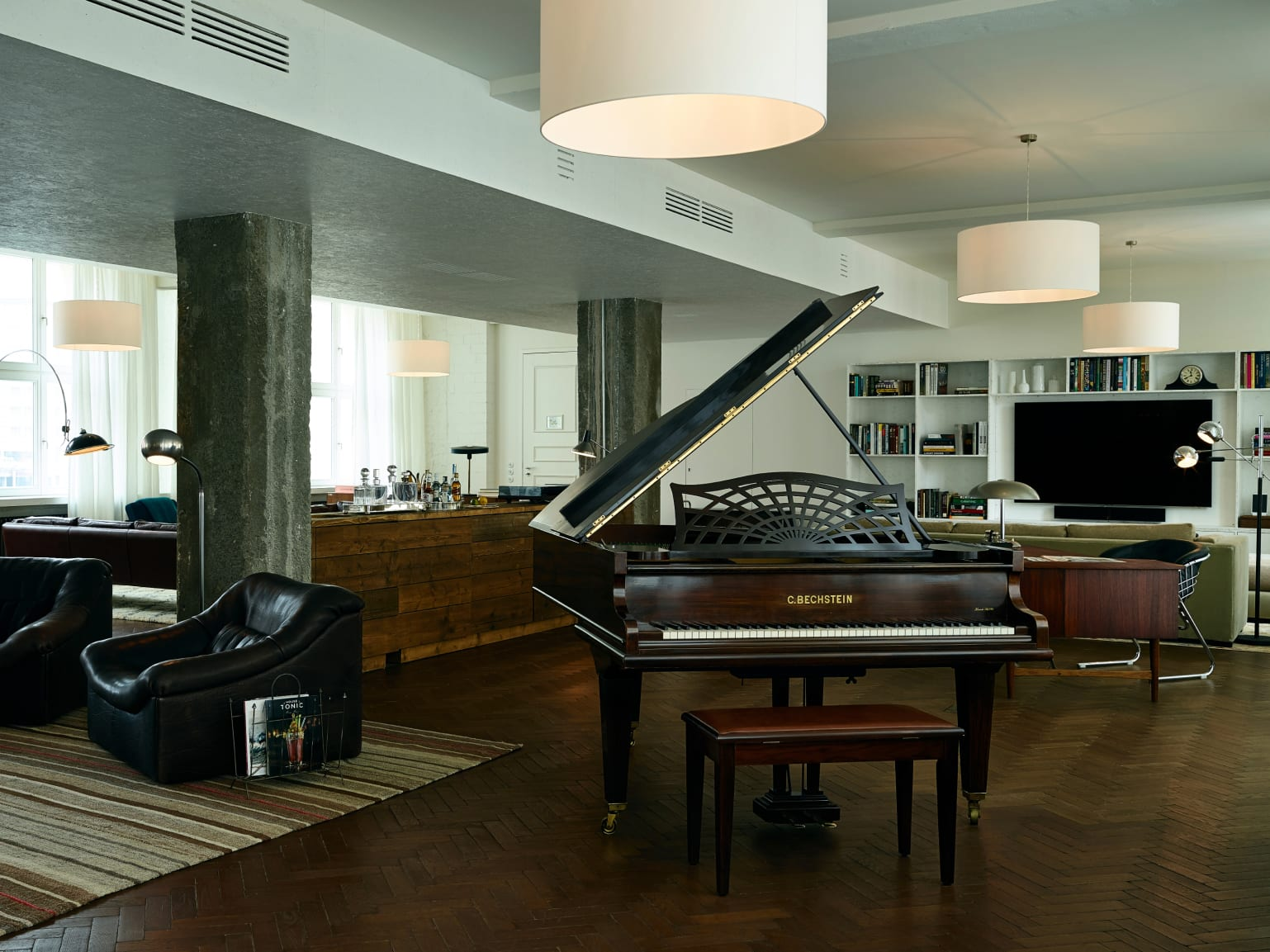 A large loft-style room with a grand piano and other items of furniture in it.