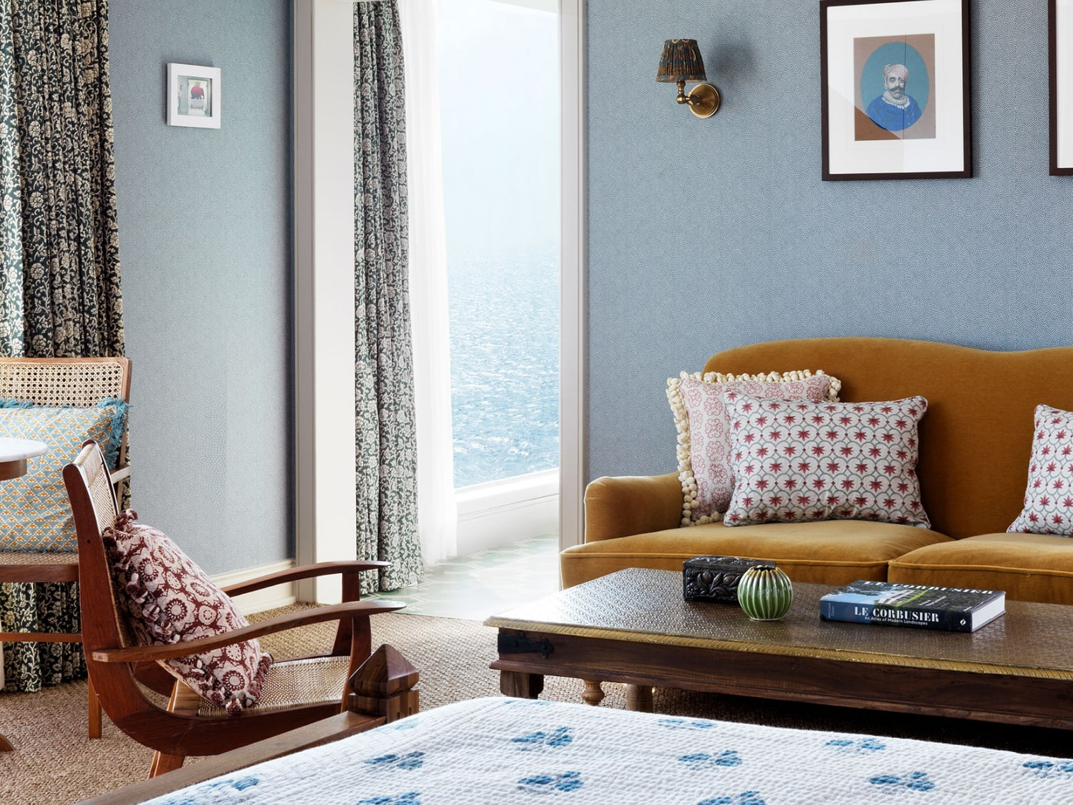 The corner of a bedroom with a doorway leading to an balcony overlooking the sea.