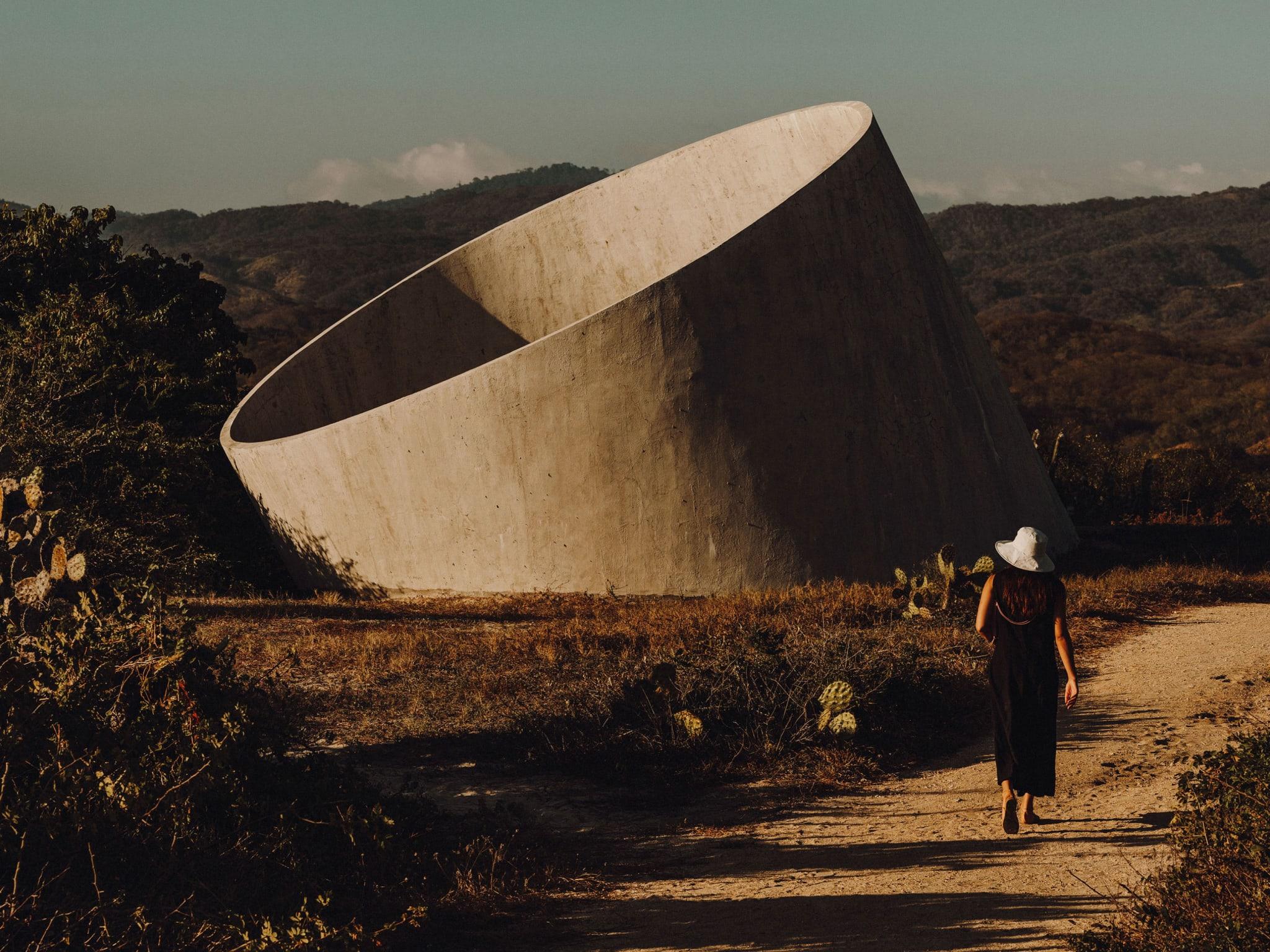 A woman walking towards a circular concrete structure.