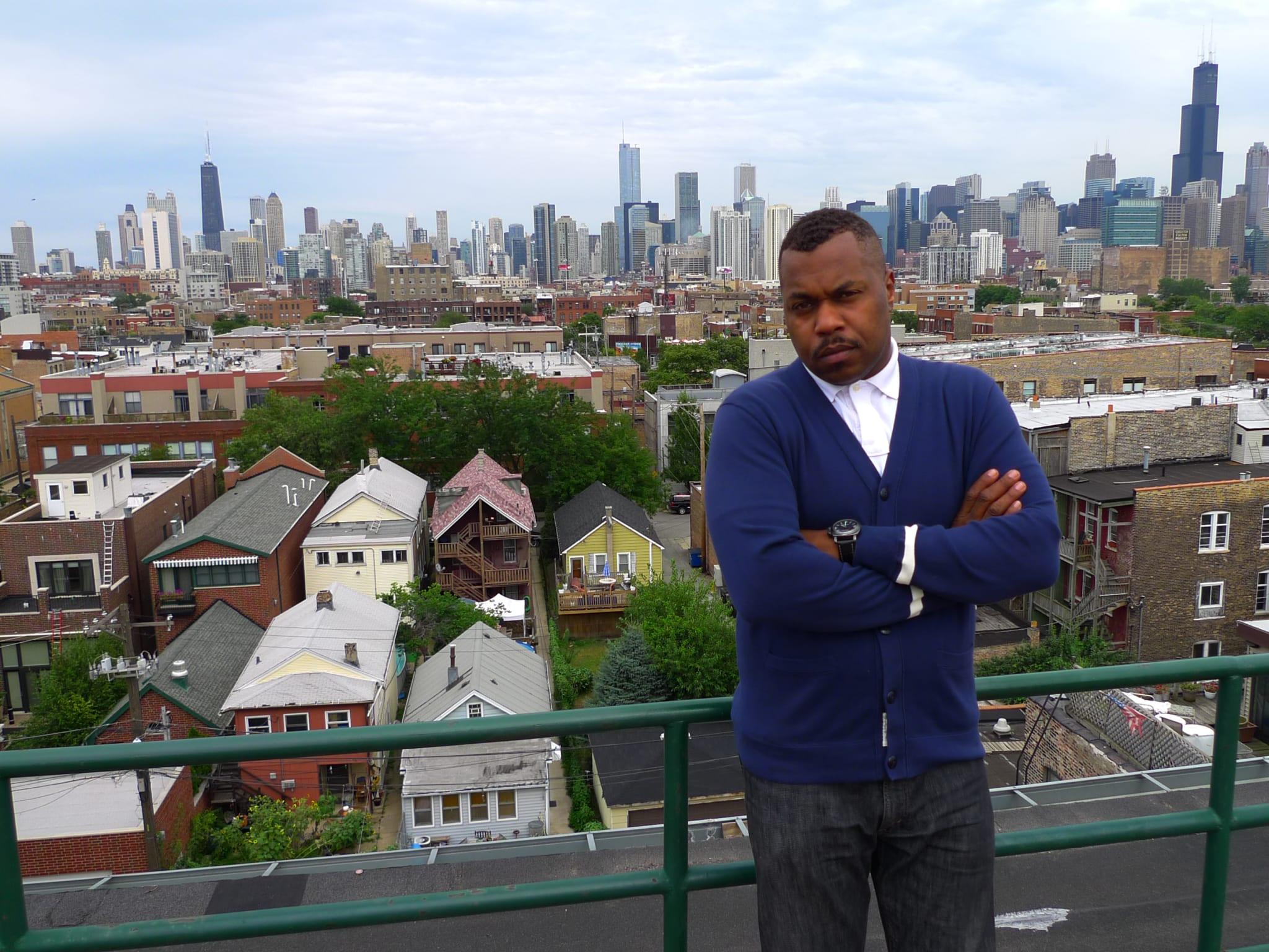 man on roof against city skyline