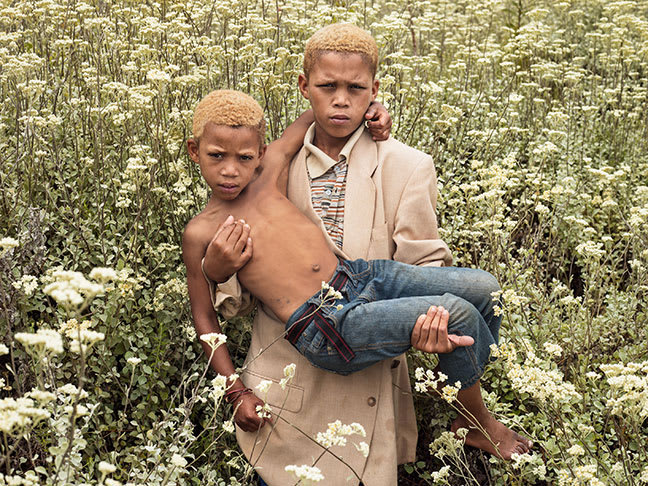 A boy carrying another boy in a wheat field.