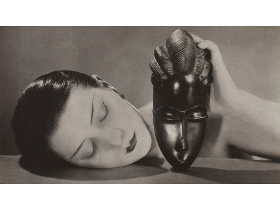 black and white image of woman lying next to a mask