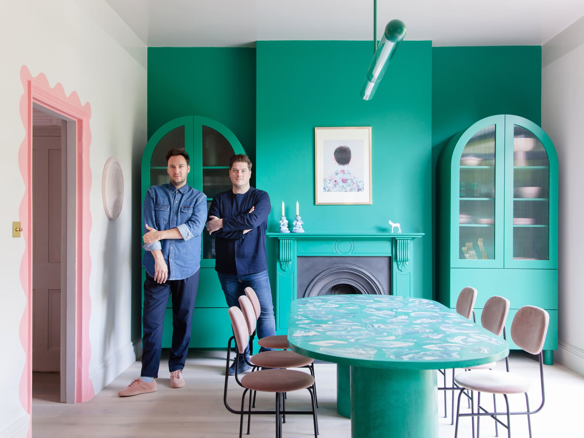 Two men standing in a room painted pink and green.