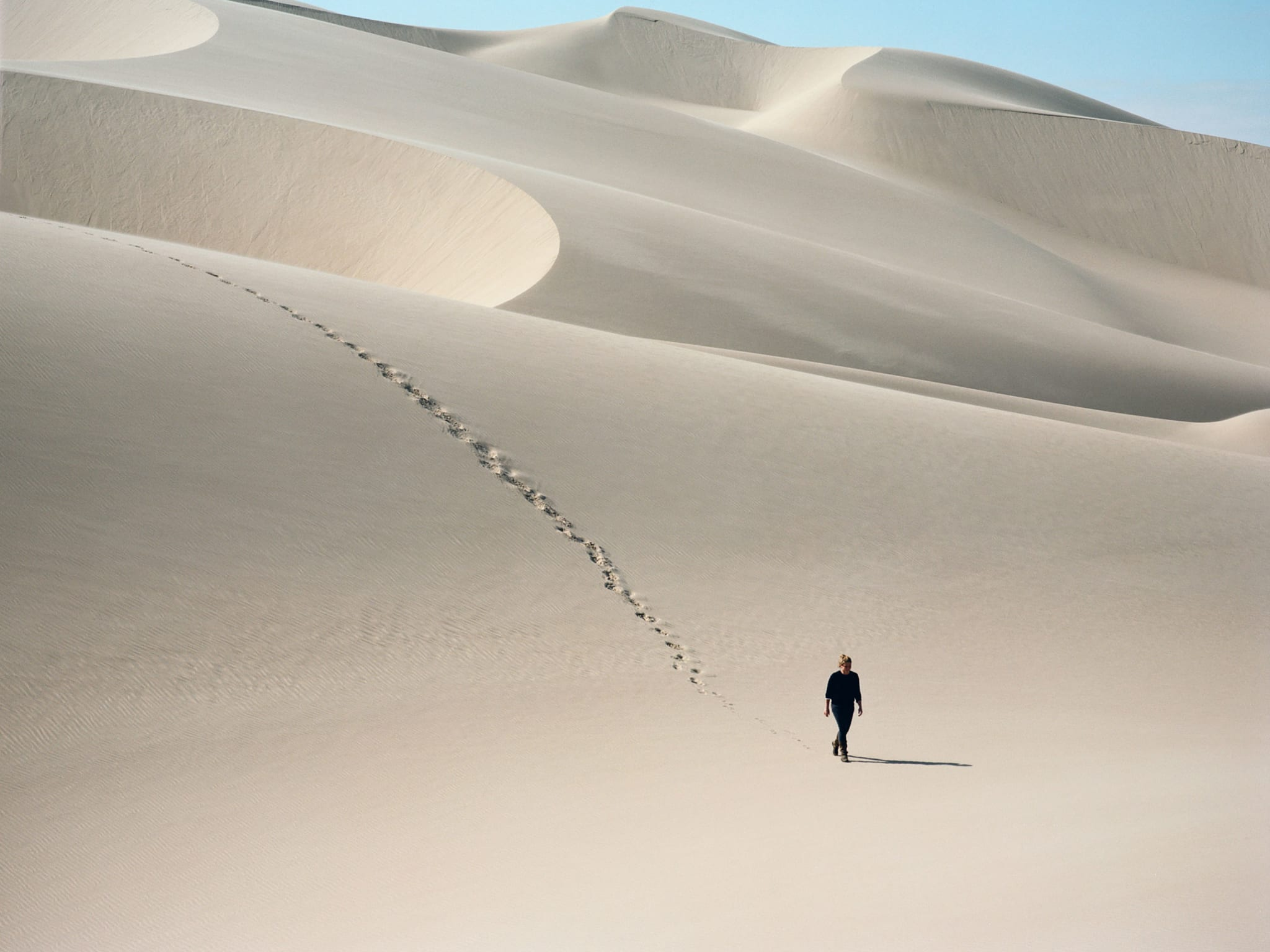 A woman walking on her own over sand dunes with her footprints trailing behind her.