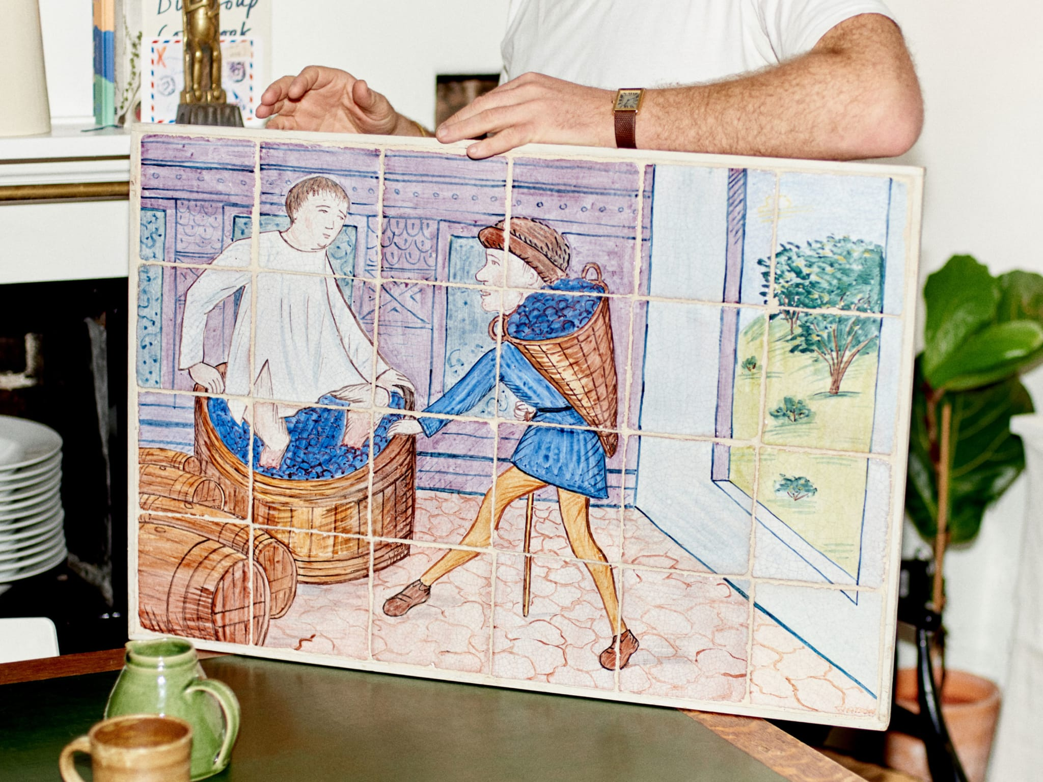 A man holding a painting on tiles.