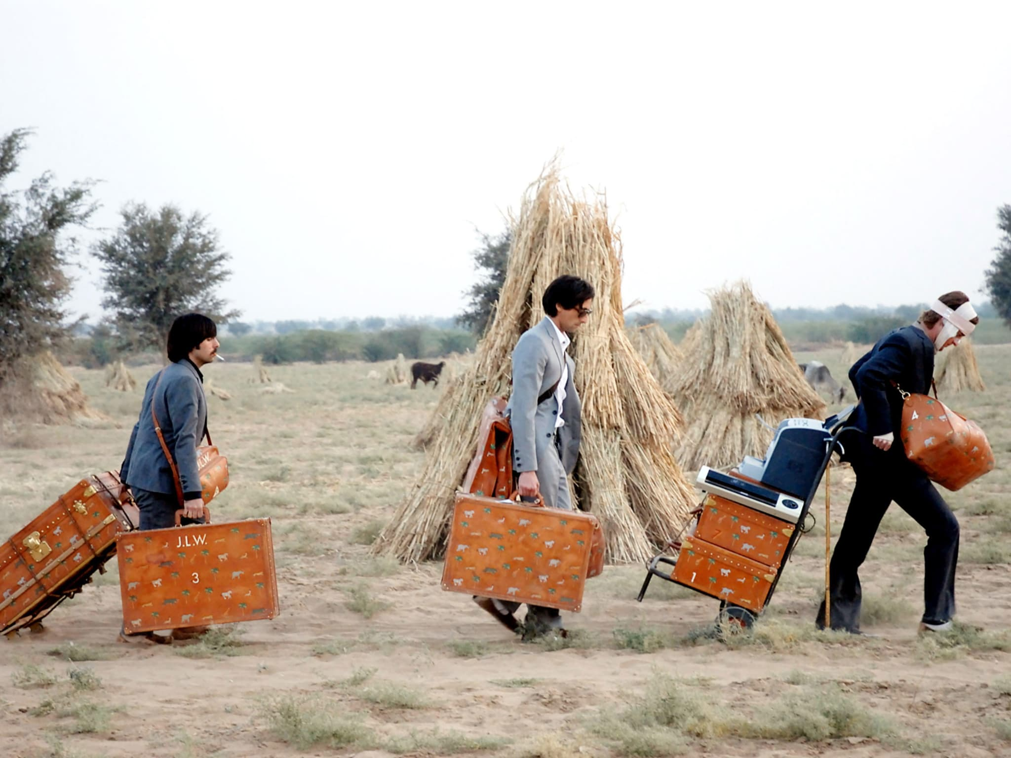 Three men pulling their suitcases through a field.