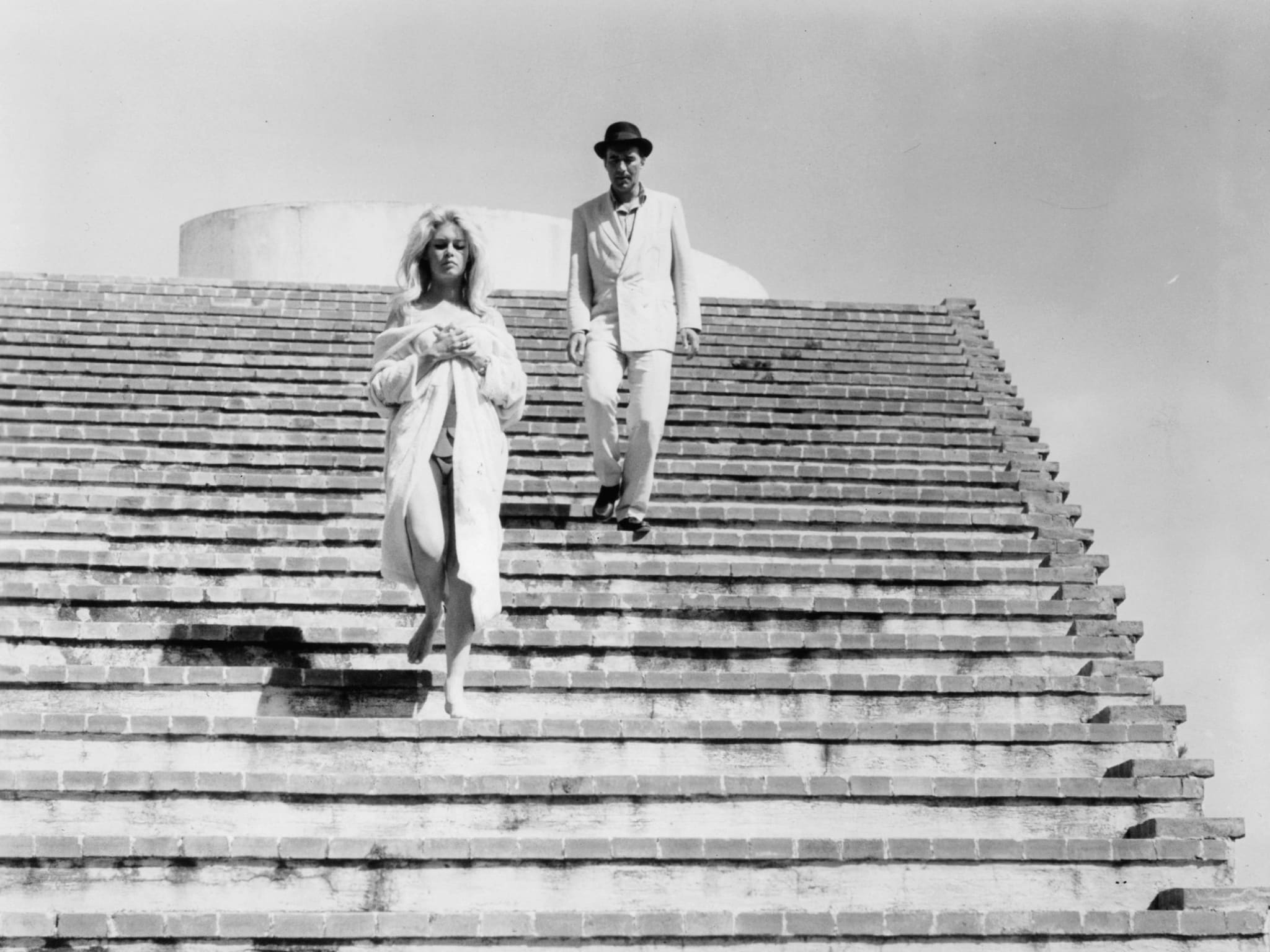 A woman and man walking down a wide outdoor staircase.