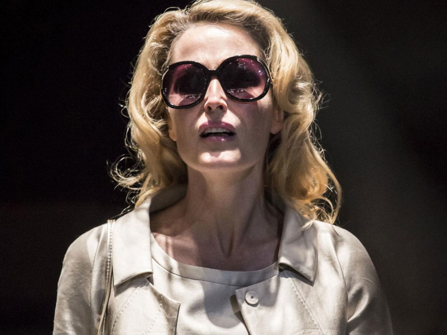 A woman with a spotlight on her wearing sunglasses.