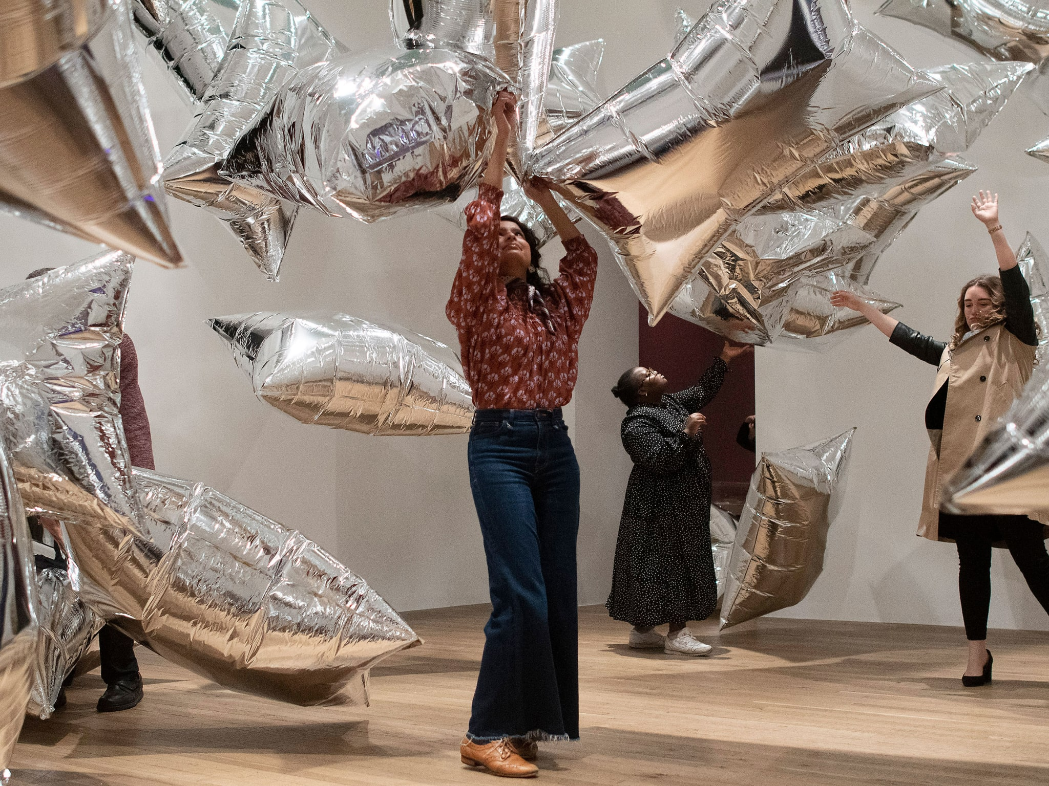 A woman bouncing silver balloons in the air in an art gallery.