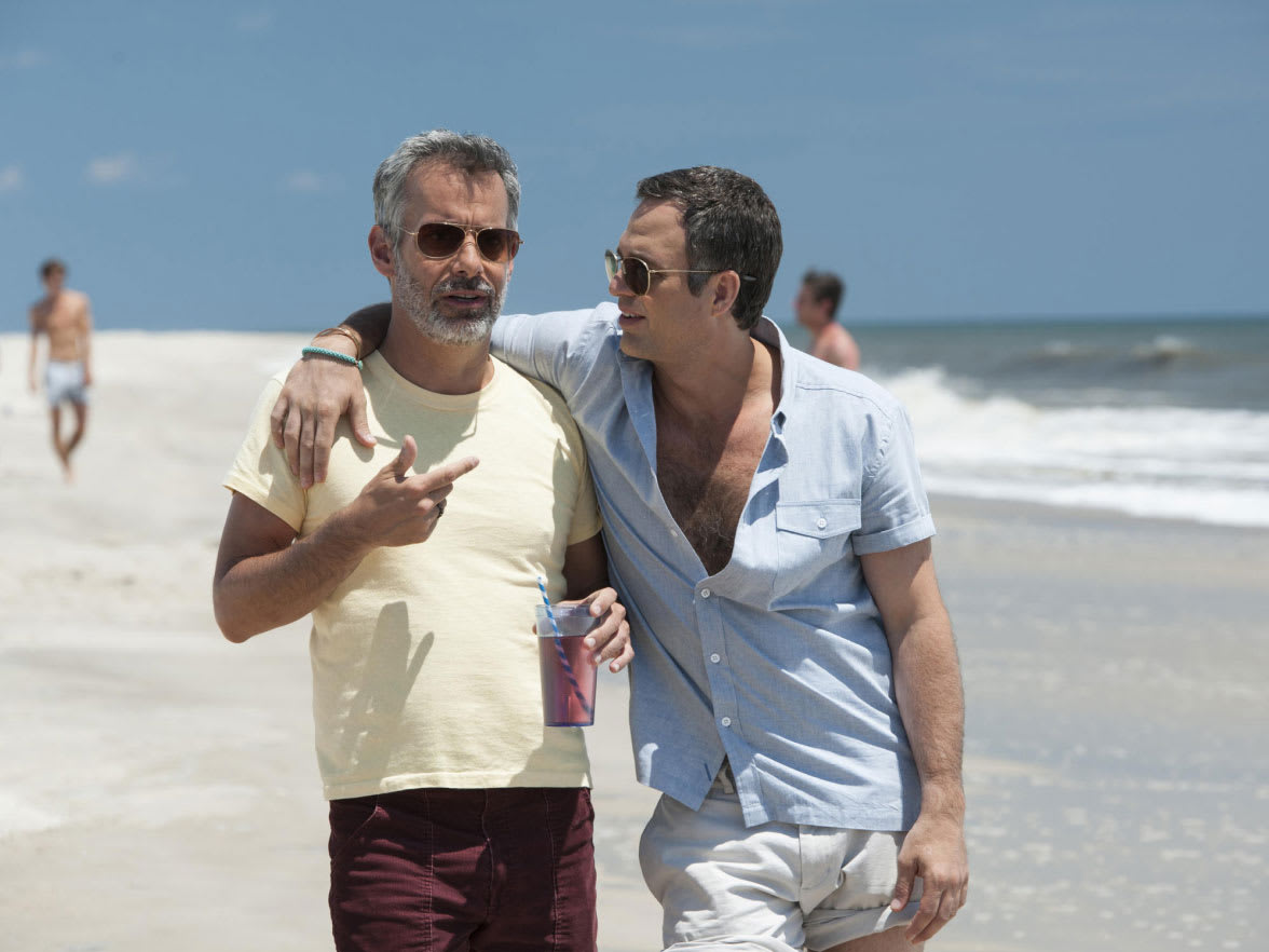 Two men walking on a beach with their arms around each other.