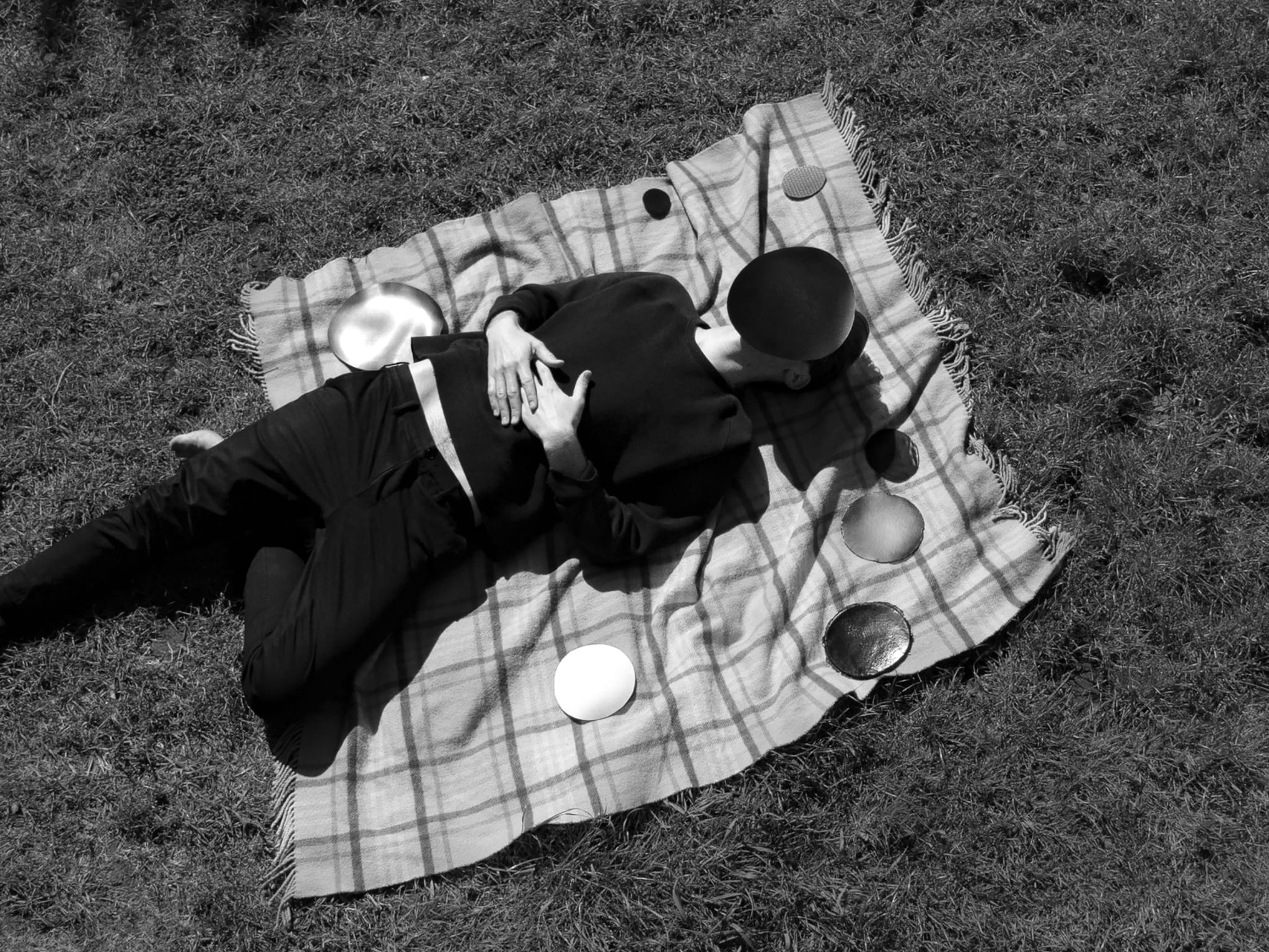 black and white photo of man lying on rug on grass