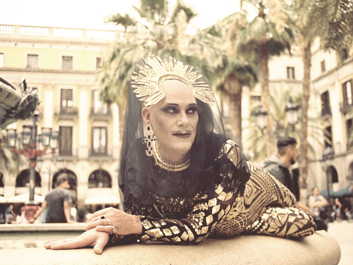 A drag queen reclining on the side of a fountain.