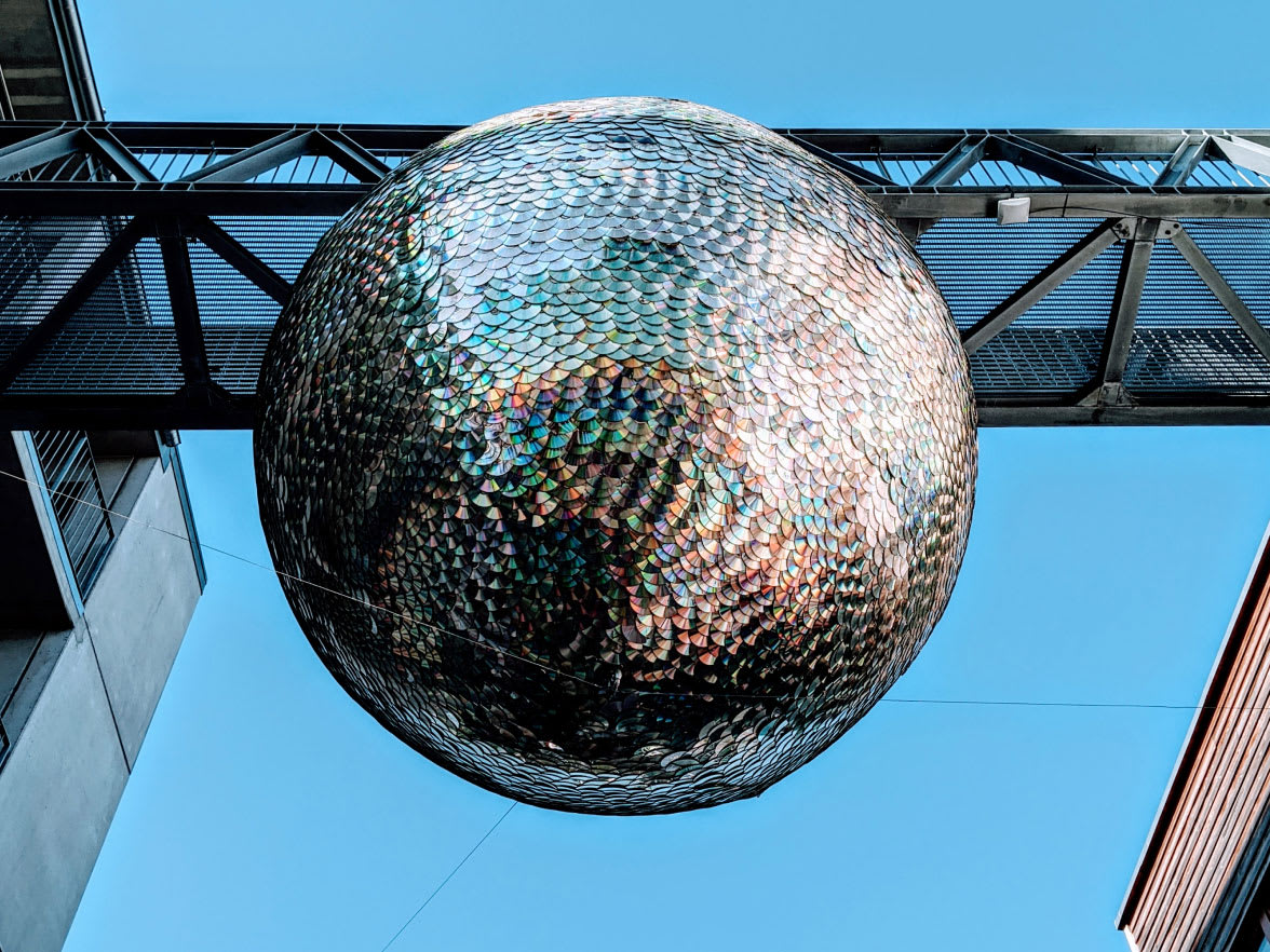A large mirrorball hanging on a structure outside.