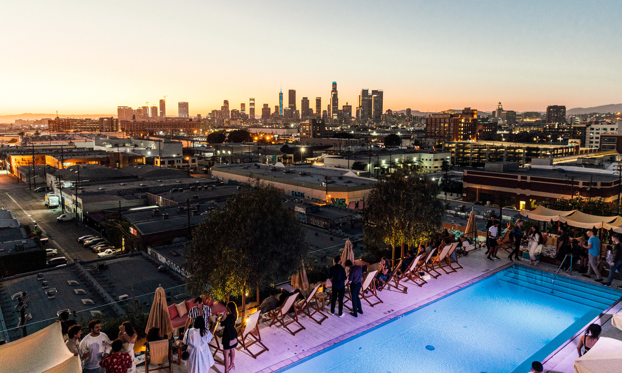 People standing around a rooftop pool at sunset with a city in the background.
