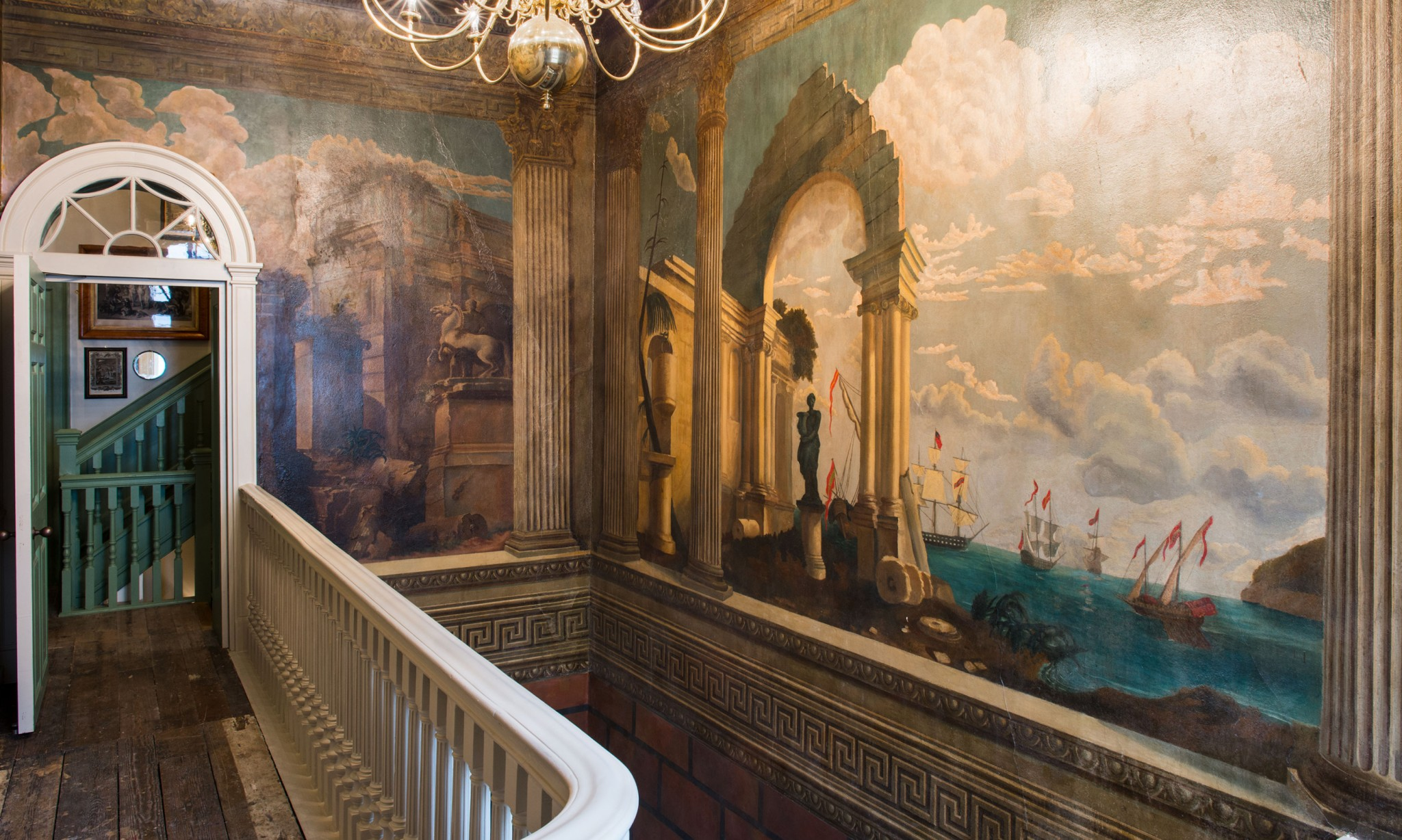 A stairwell with murals painted on the walls.