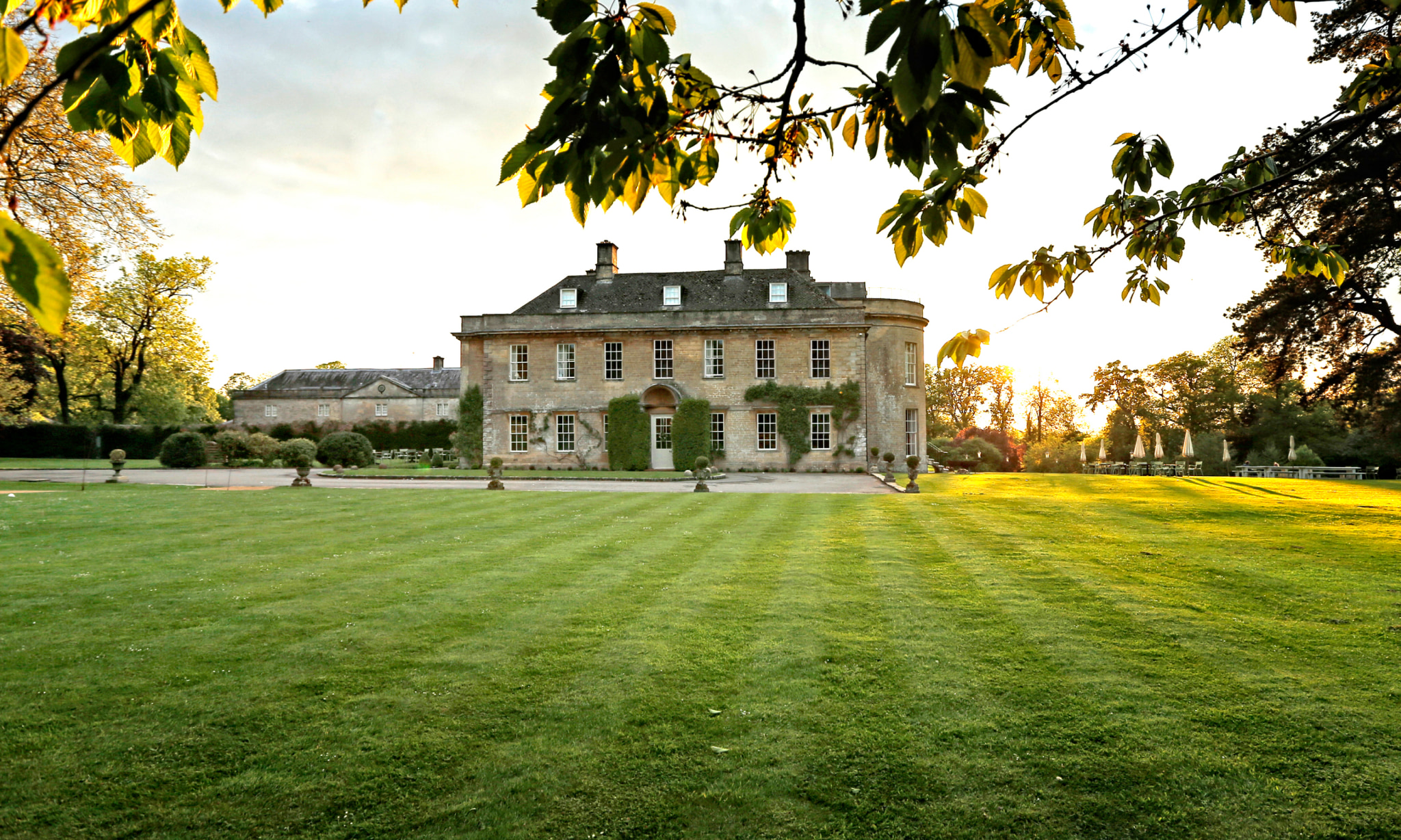 A country house and grounds at sunrise.
