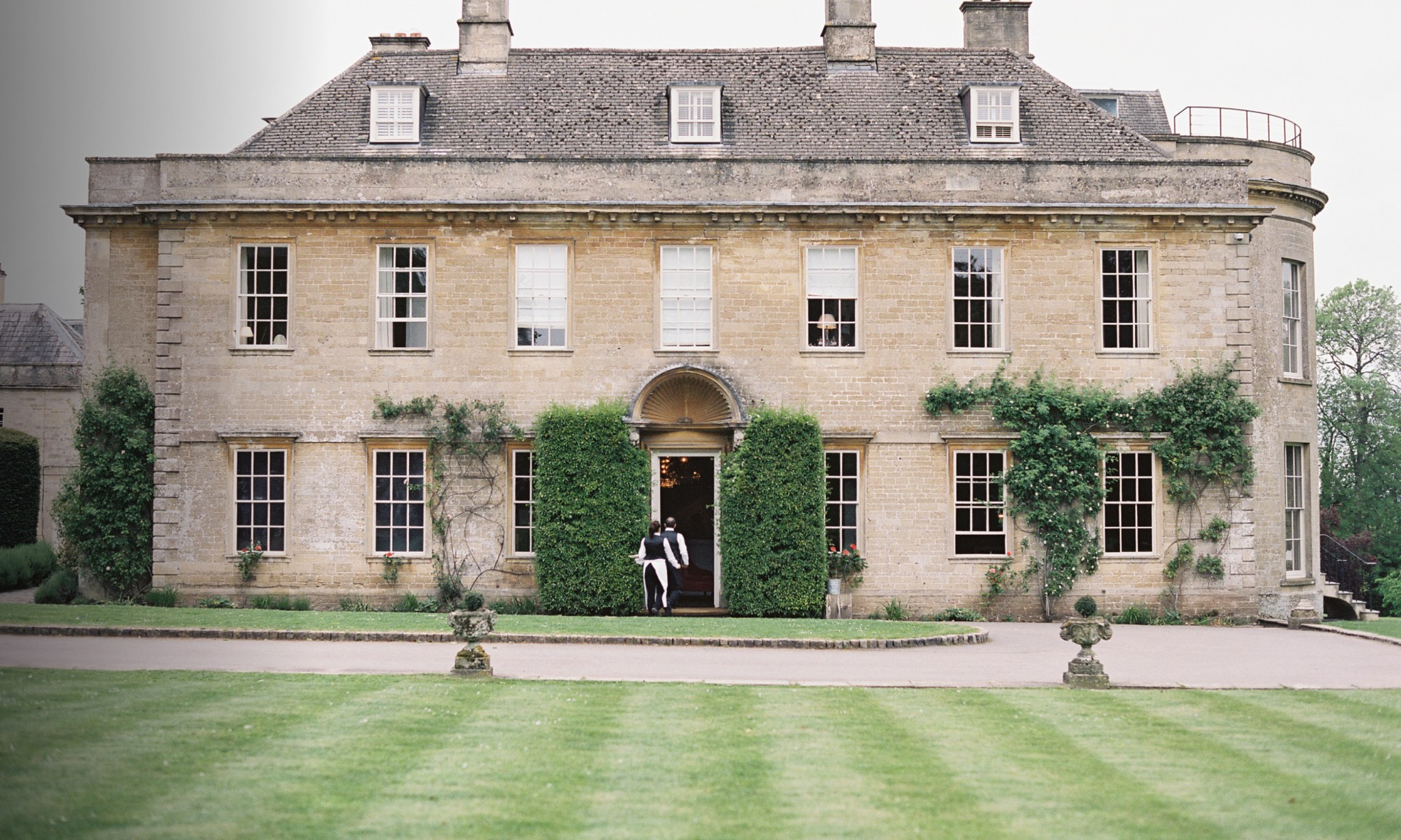 A large country house with waiters entering.