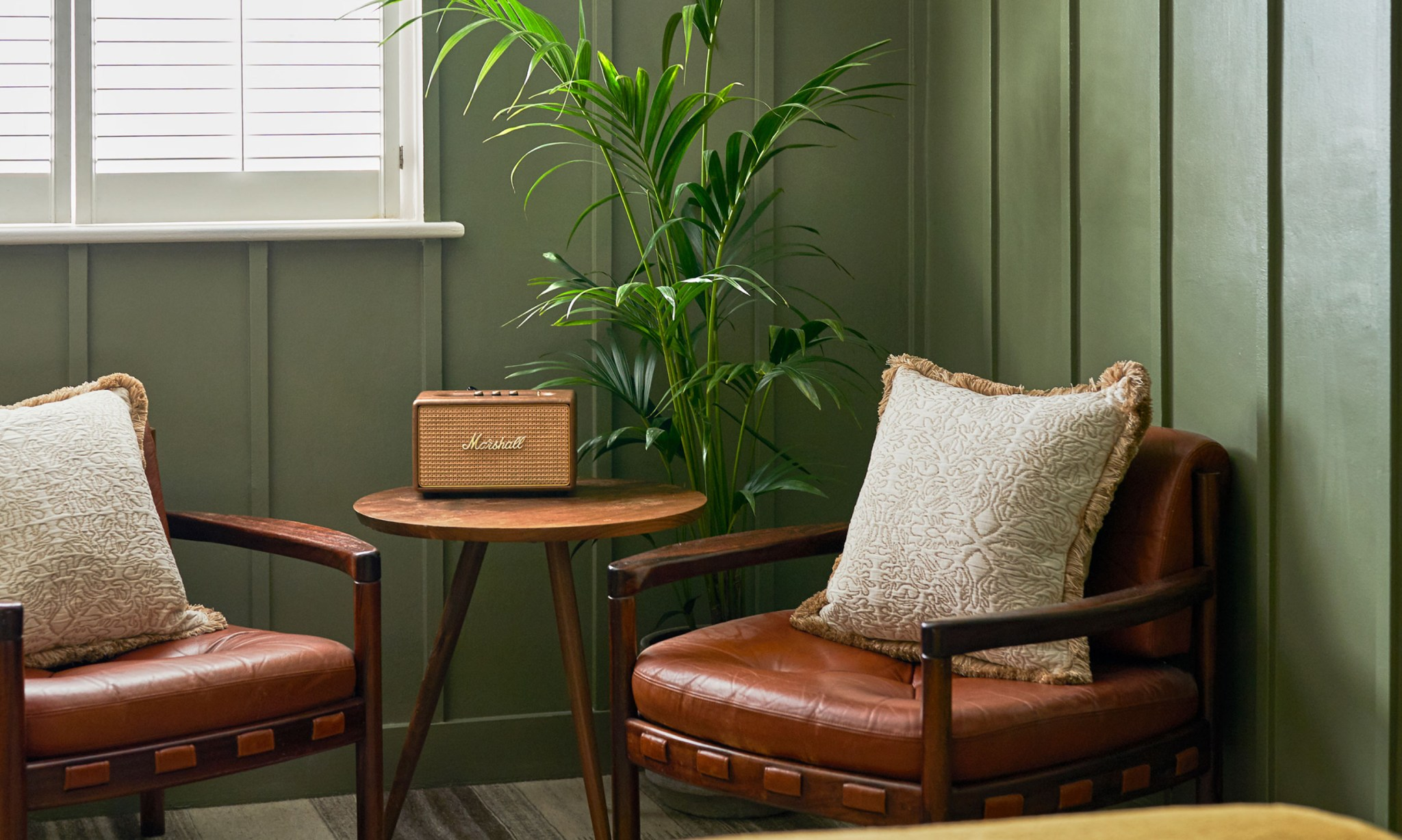 A bedroom's lounging area with two armchairs, a table, portable speaker and a plant.
