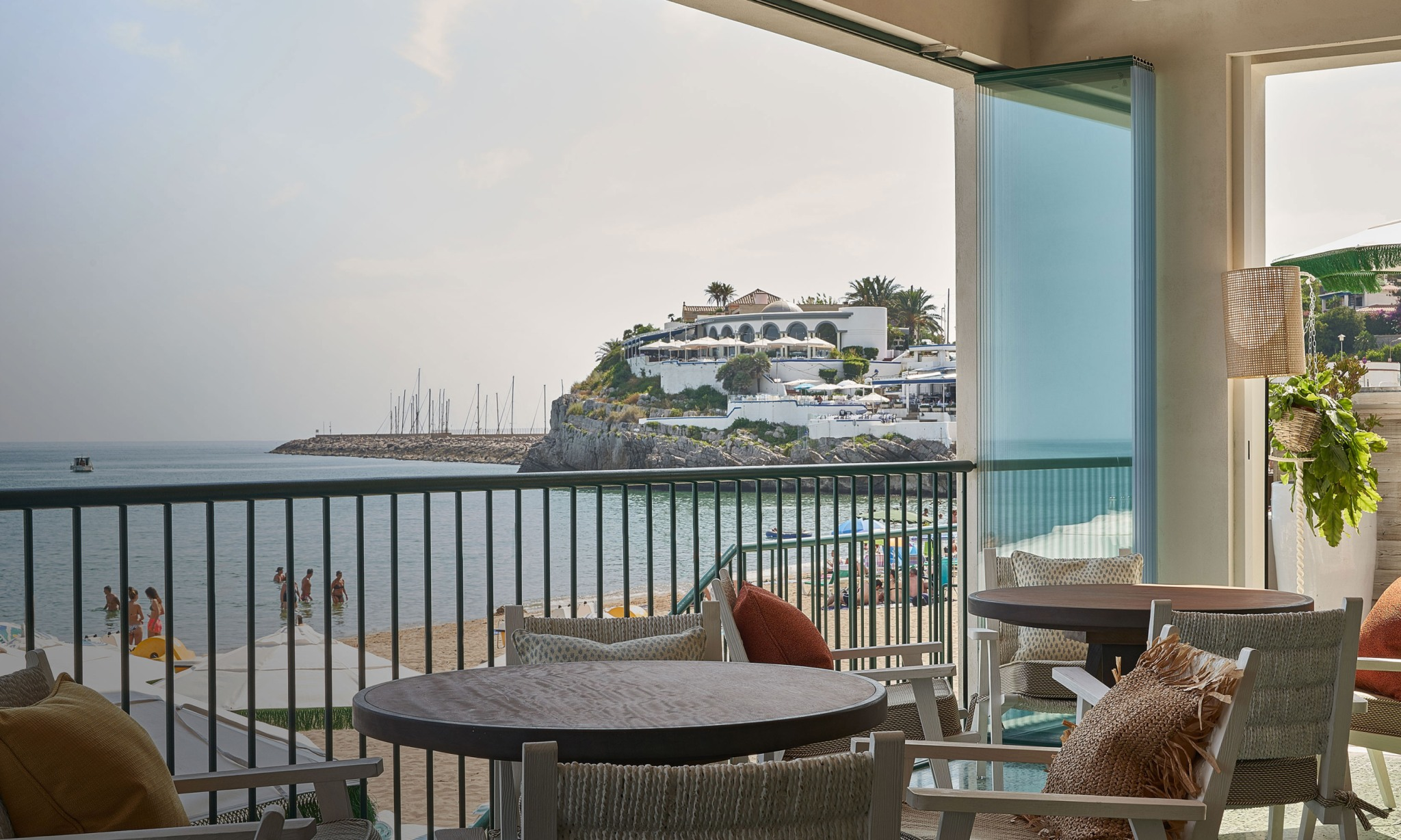 An indoor seating area looking over a beach and the sea.
