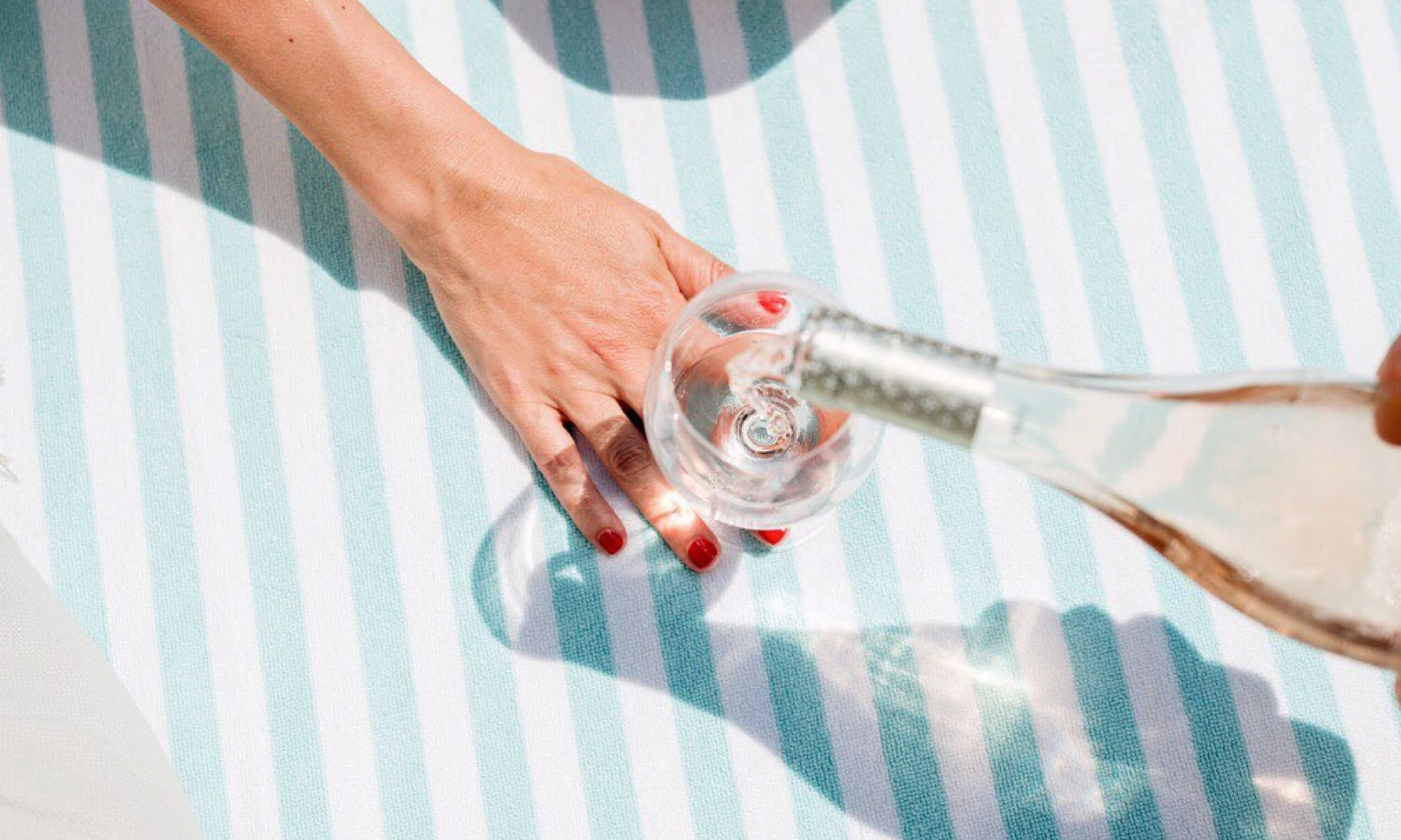 A hand steadies a glass with wine being poured into it.