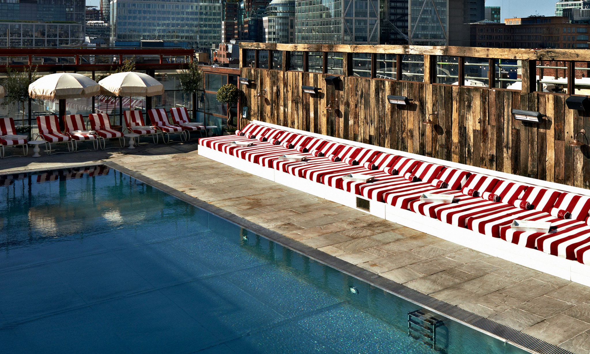 A rooftop pool with red and white striped sun loungers and day beds.