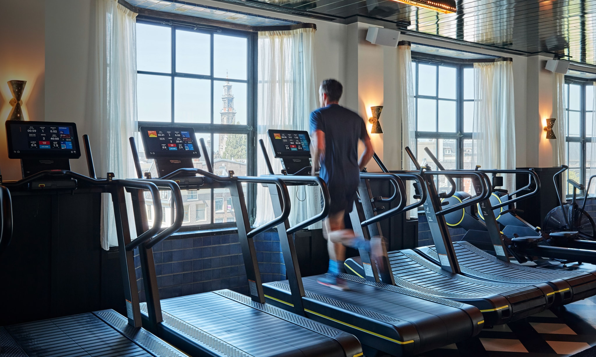 A man running on a running machine while looking out of a window.