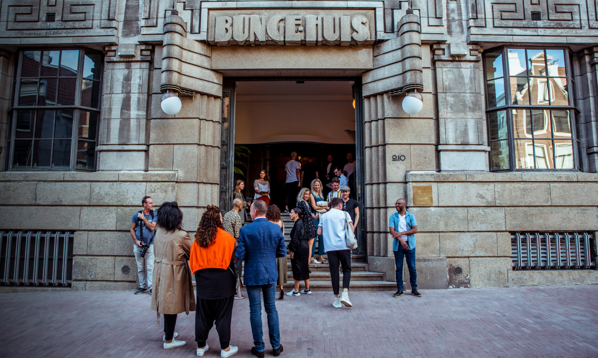 People mingle outside an entrance to a building with Bungehuis written above the doorway.