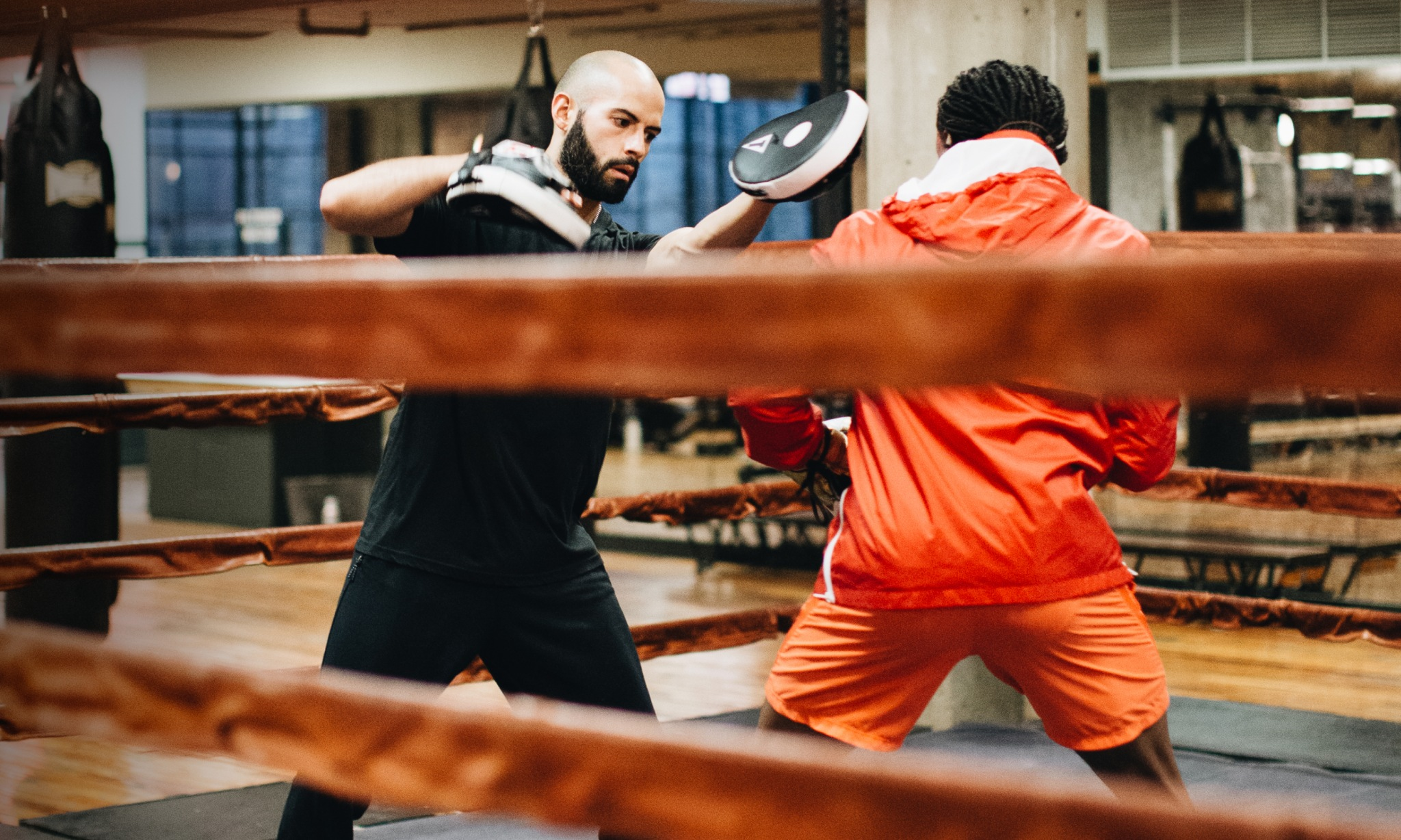 A trainer and a boxer sparring in a ring.