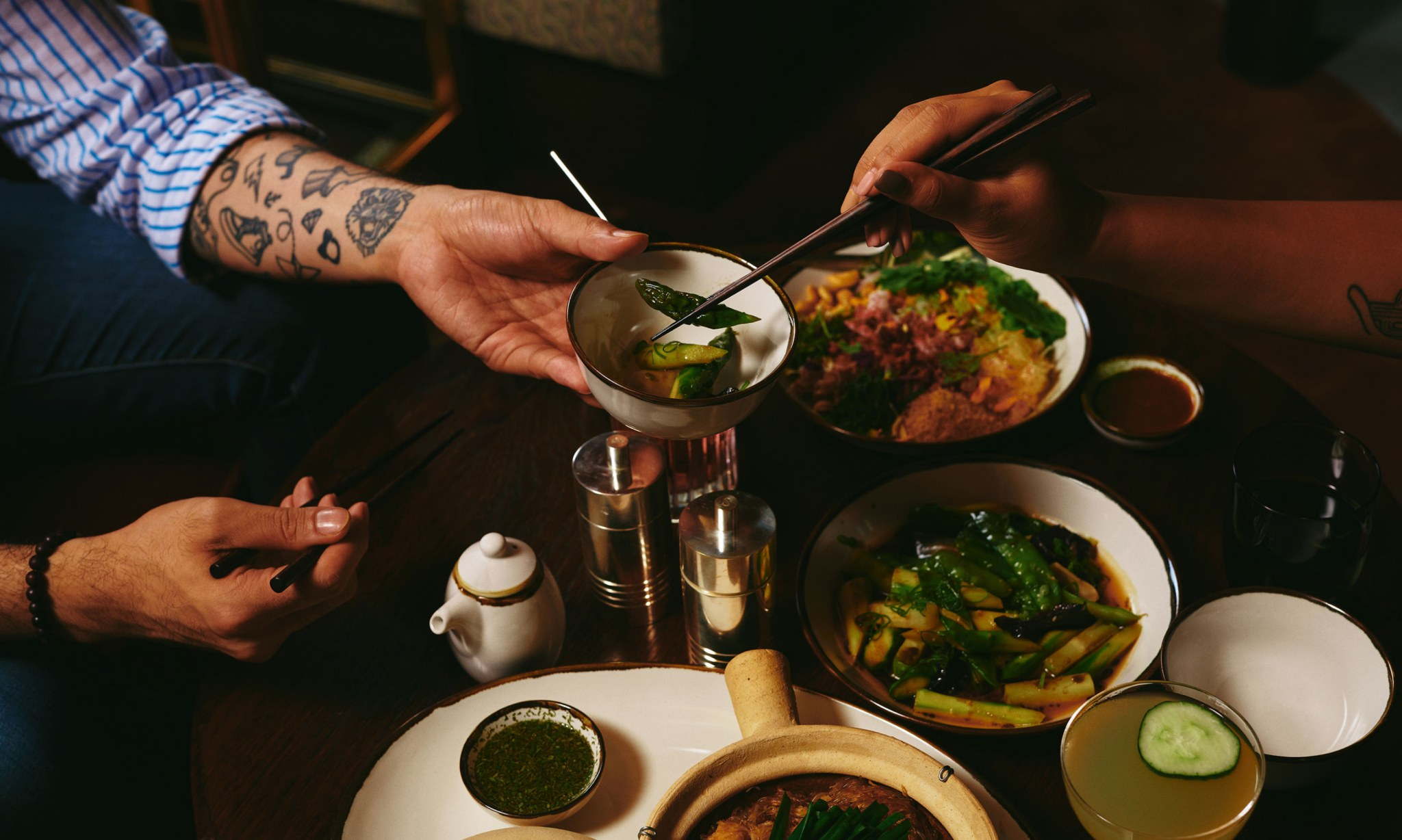 A man and a woman share Asian food.