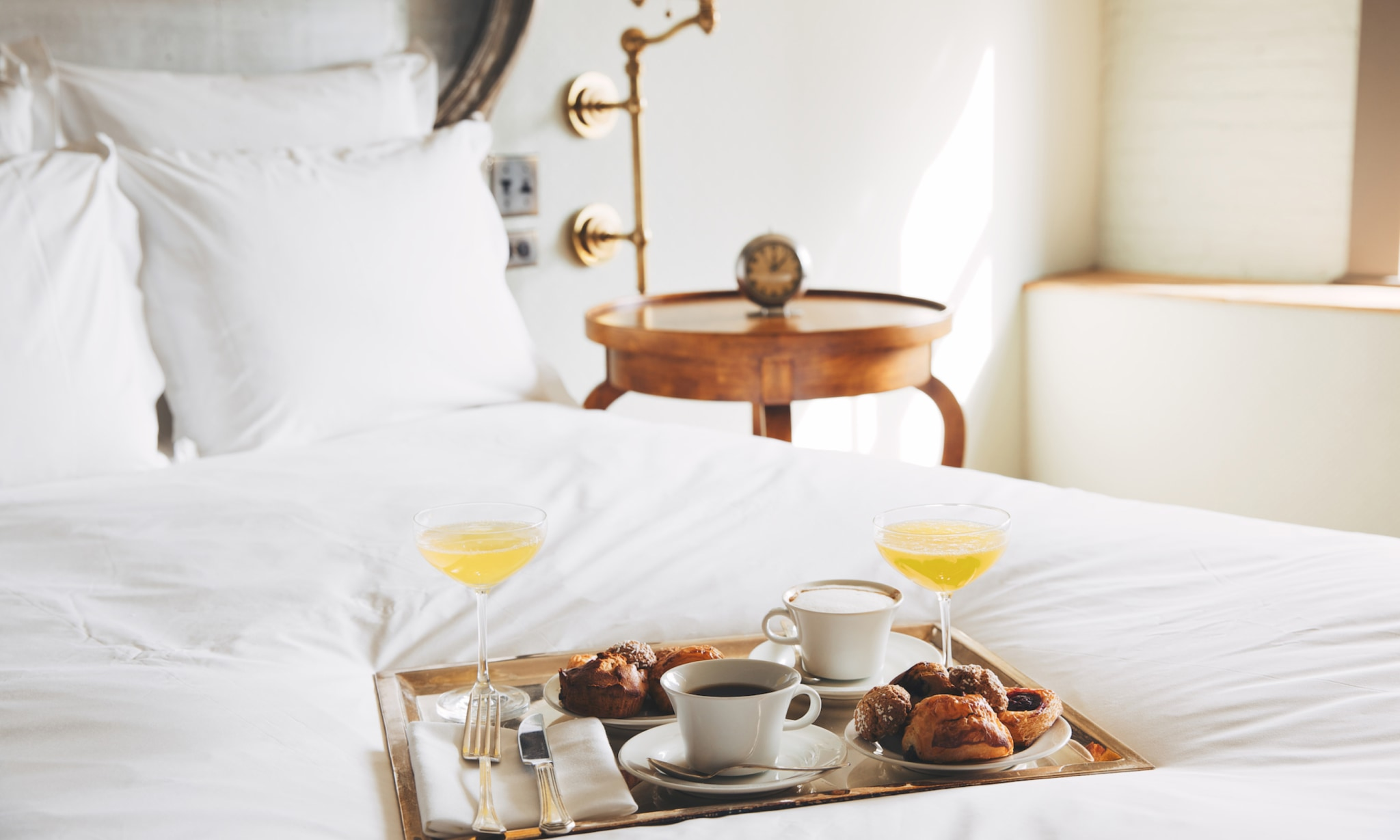 A bed with white bed linen and a tray of room service breakfast on it.