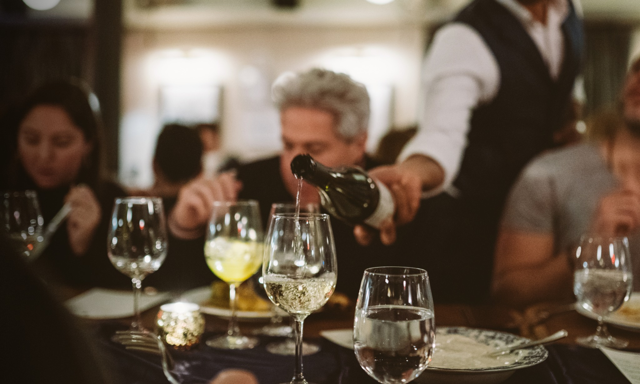 A waiter serves wine to a table of diners.