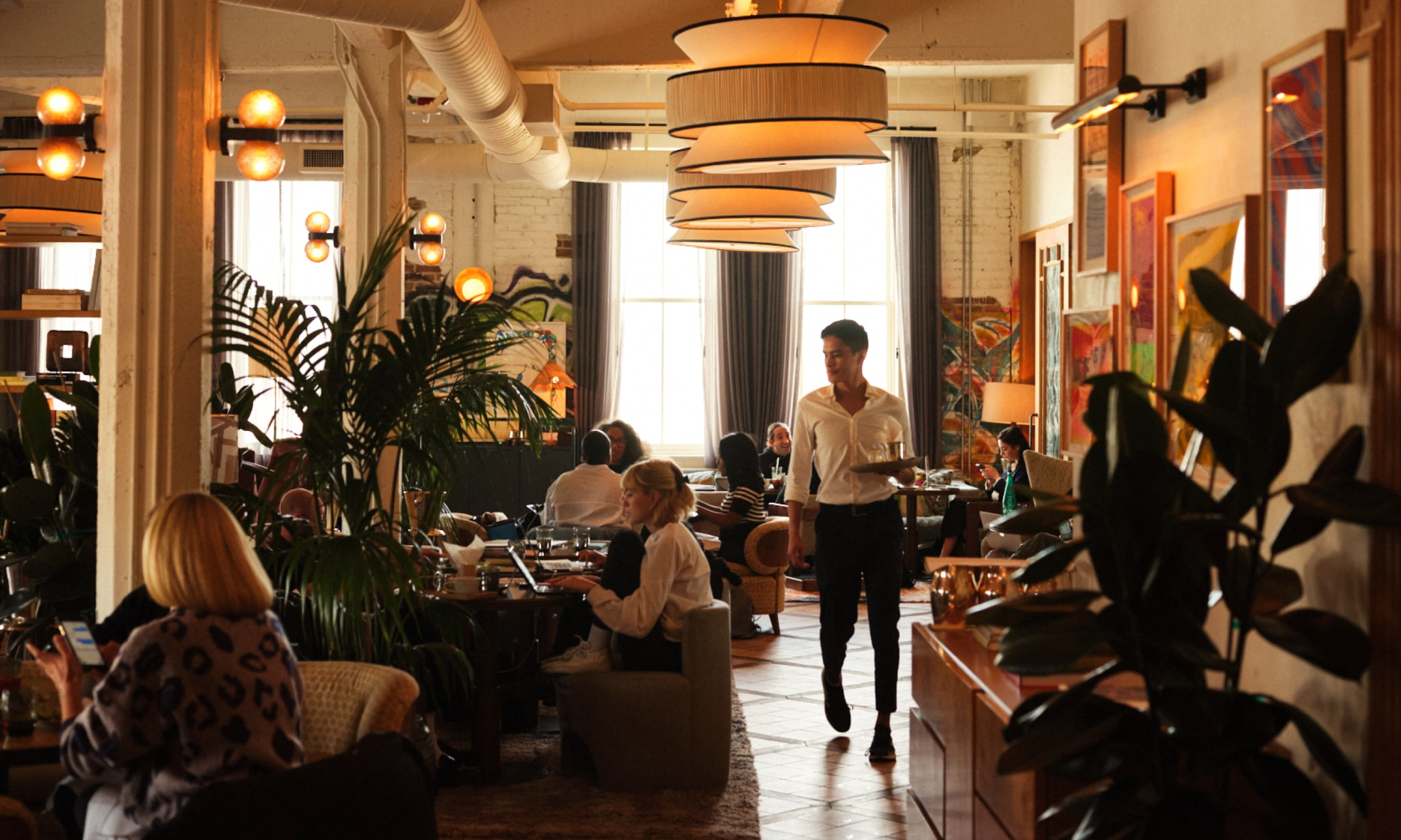A waiter serving people in a relaxed dining area.