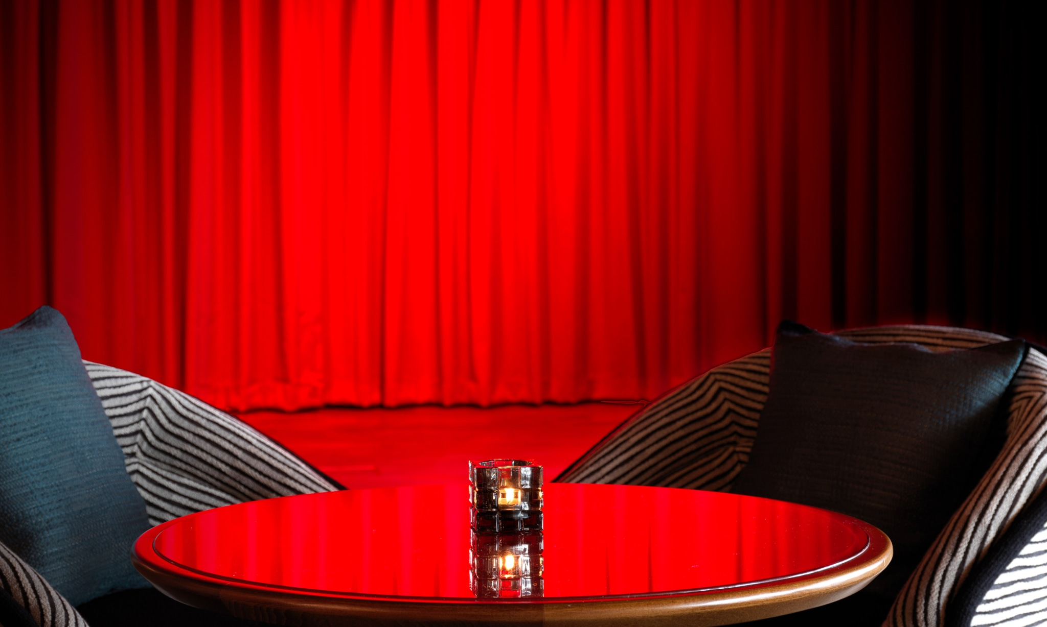 A stage is bathed in red light by a table and chairs.