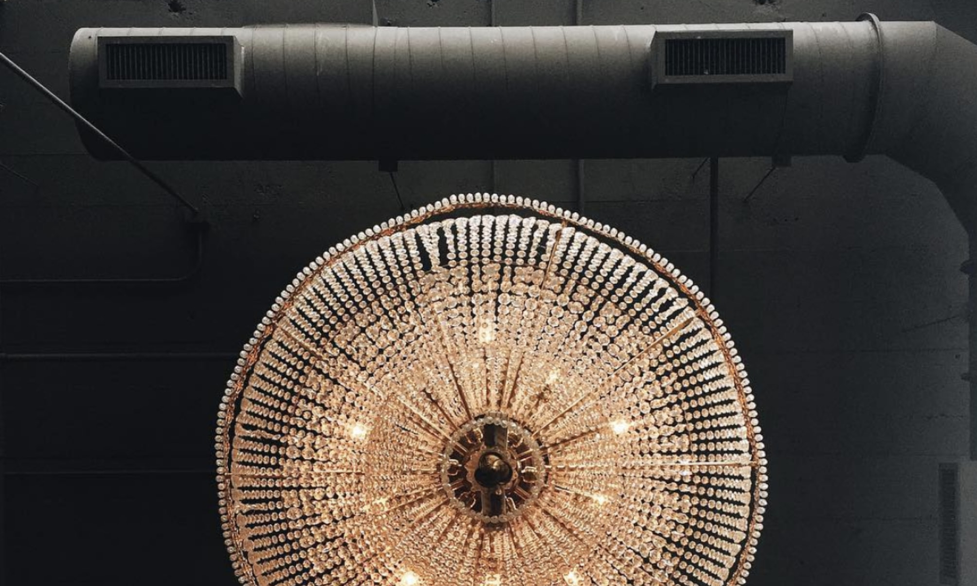 A chandelier and air conditioning pipe attached to a ceiling.