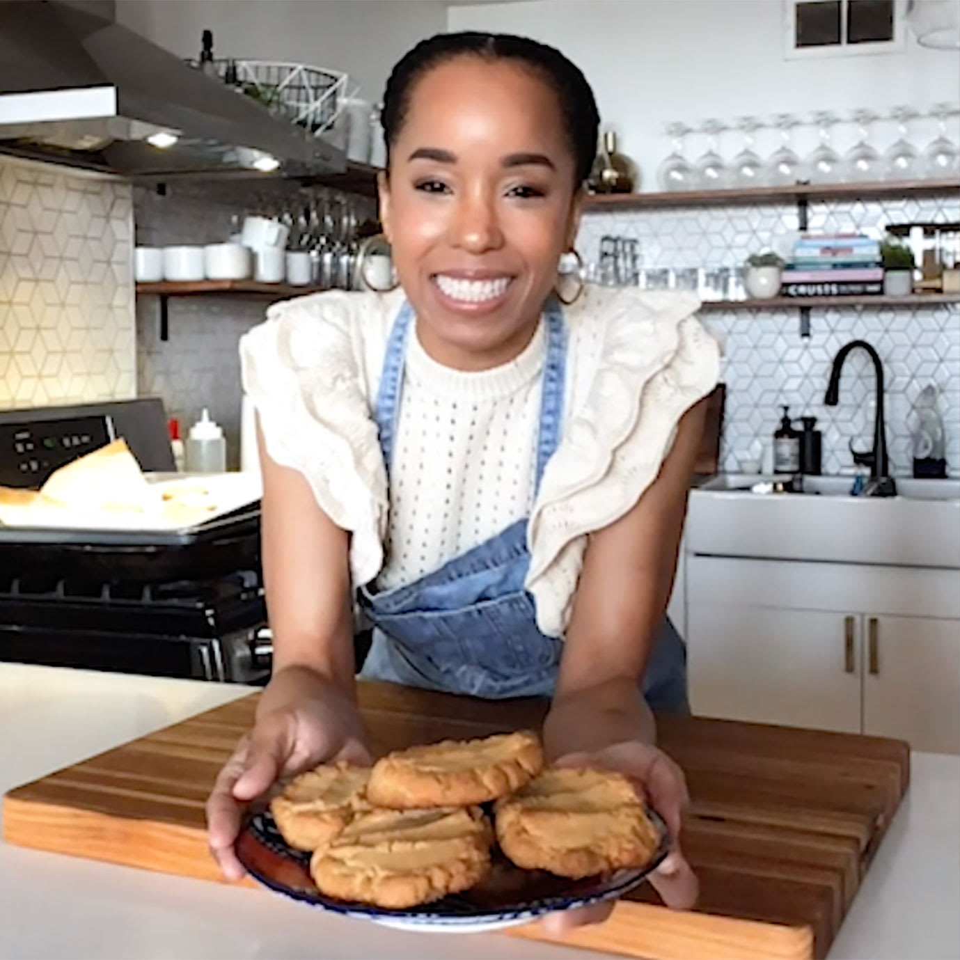 A woman in a kitchen holding a plate of cookies.