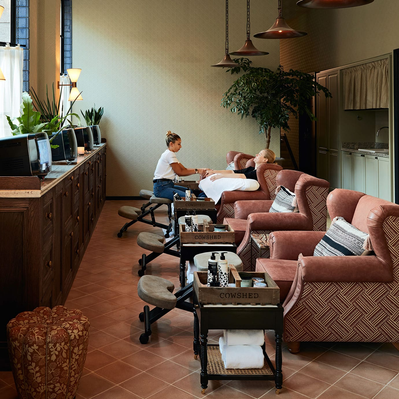 A row of treatment chairs in a spa with a woman receiving treatments from other women.
