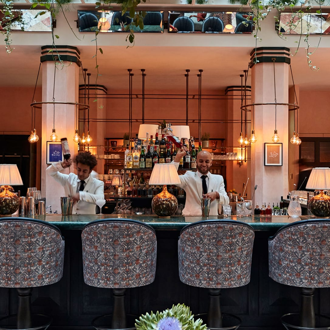 Two barmen in white jackets pour cocktails in a restaurant bar.